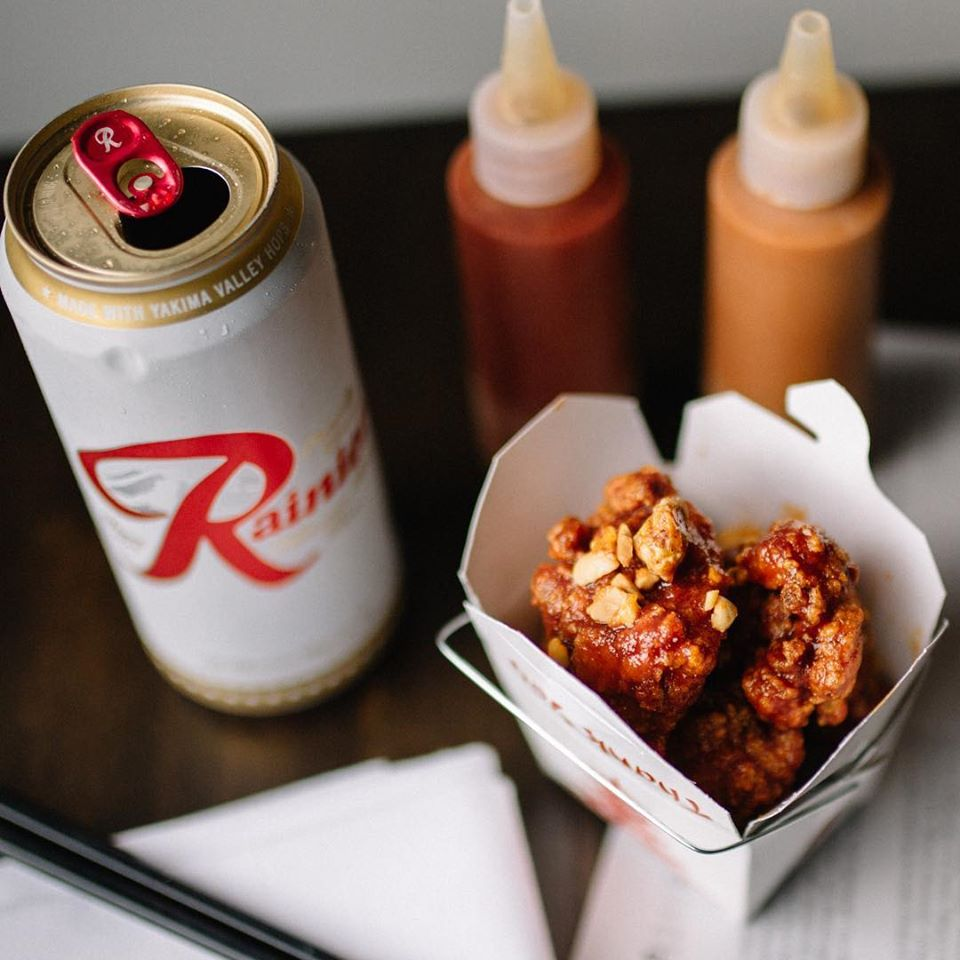 A picture of a Chinese food container full of fried chicken with a Rainier can and squeeze bottles of sauces at Revelry
