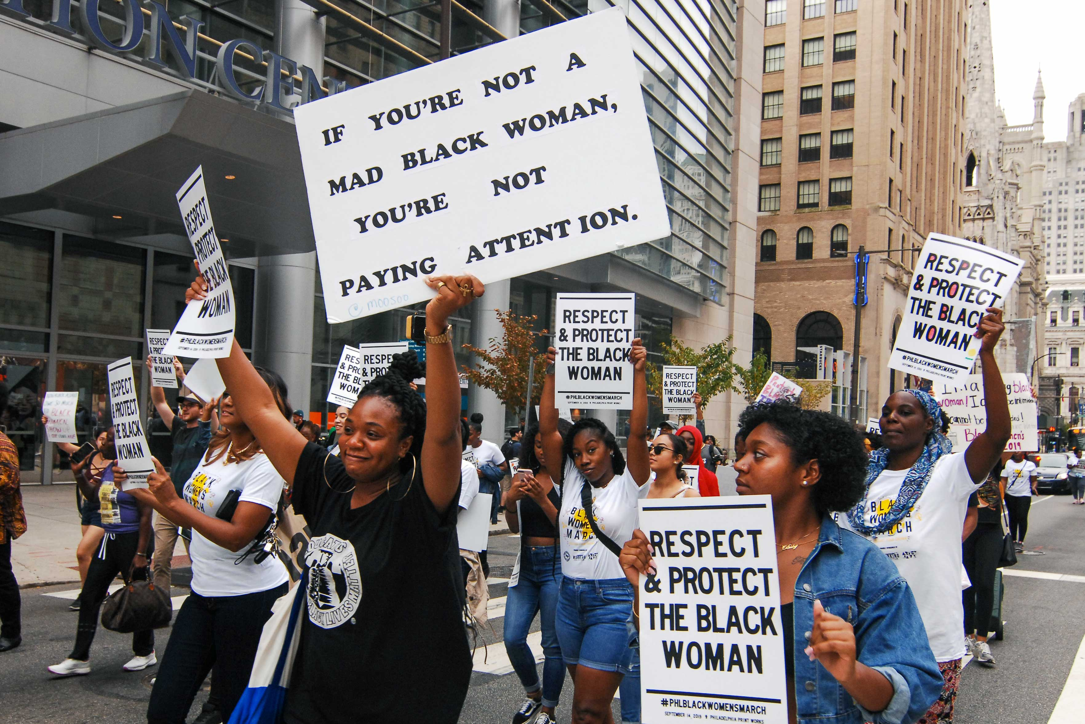 "Black women marching down a street holding signs that read, ""Respect & protect the black woman,"" and, ""If you're not a mad black woman, you're not paying attention."""