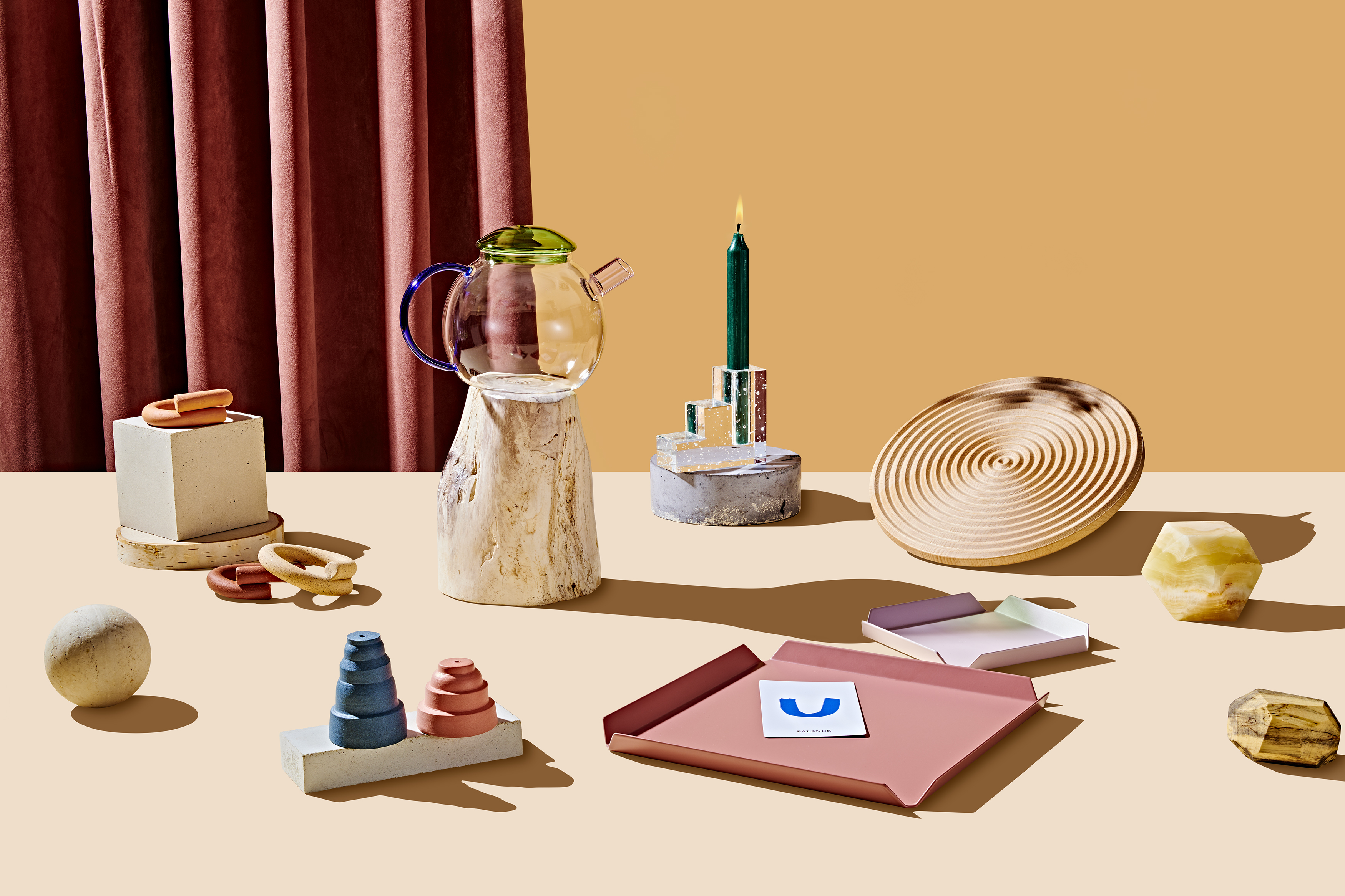 A grouping of objects arranged on a table for the Curbed Holiday Gift Guide 2019. There is a teapot, candleholder, cutting board, tarot card, salt and pepper shakers, napkin rings, and other objects. In the background is a mauve curtain and a yellow wall.