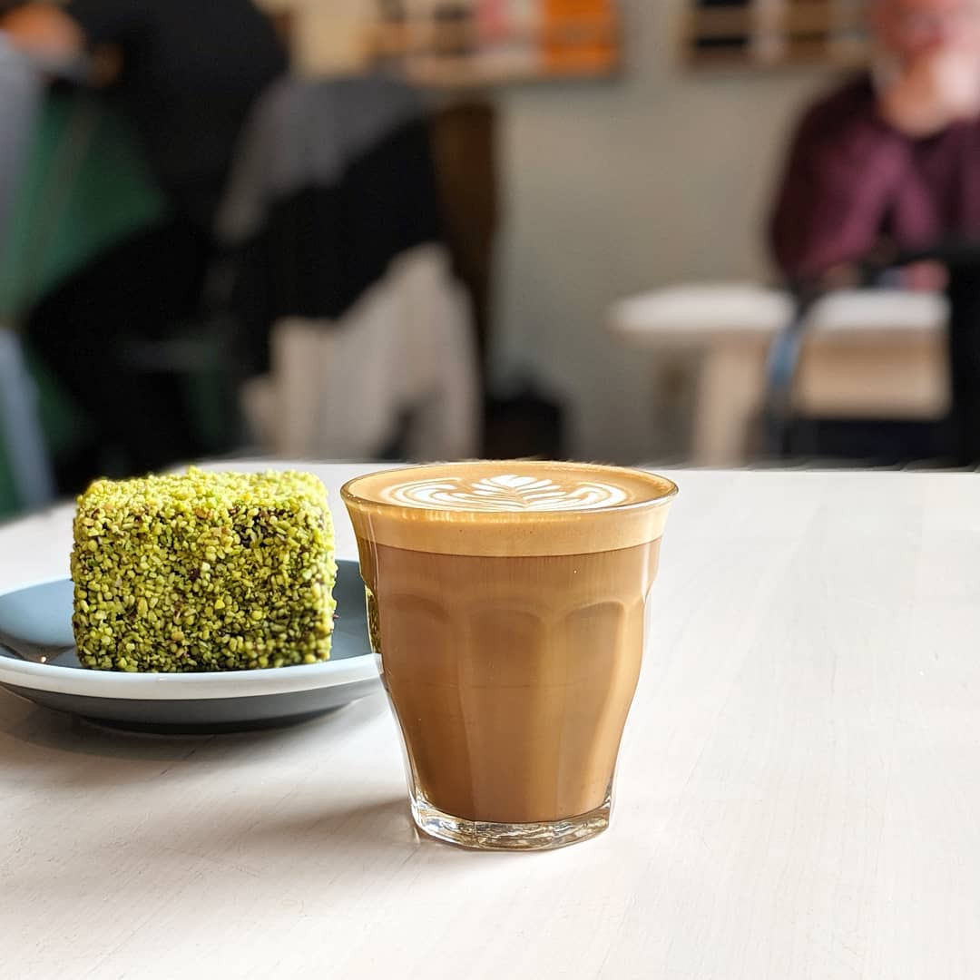 A latte next to a pastry on an outdoor table.