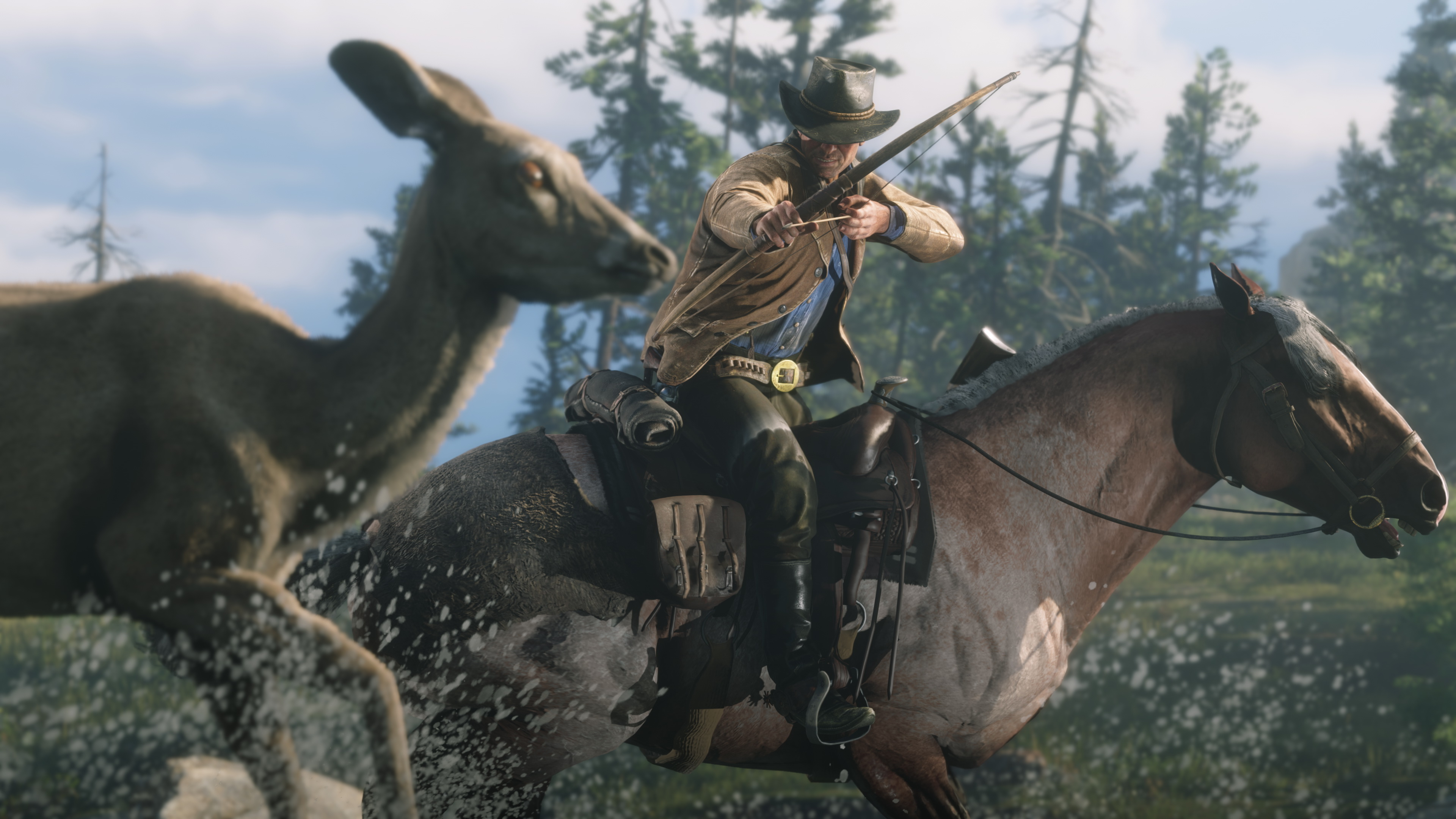 a man in a cowboy hat and tan jacket, Arthur Morgan, aims a bow at a deer while he's riding through shallow water in Red Dead Redemption 2