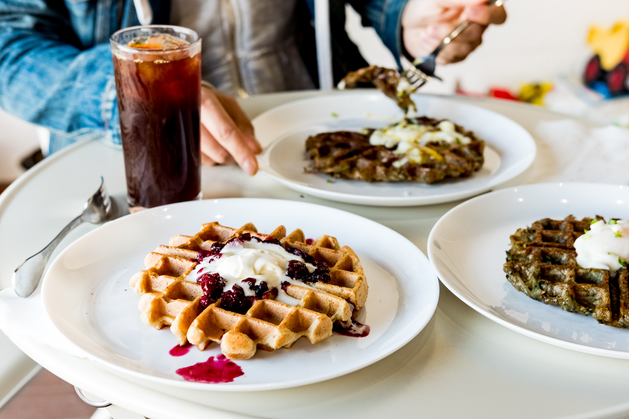 Three plates of waffles. Two appear to be made with darker batter and the other is a lighter color with a berry compote topping and cream.