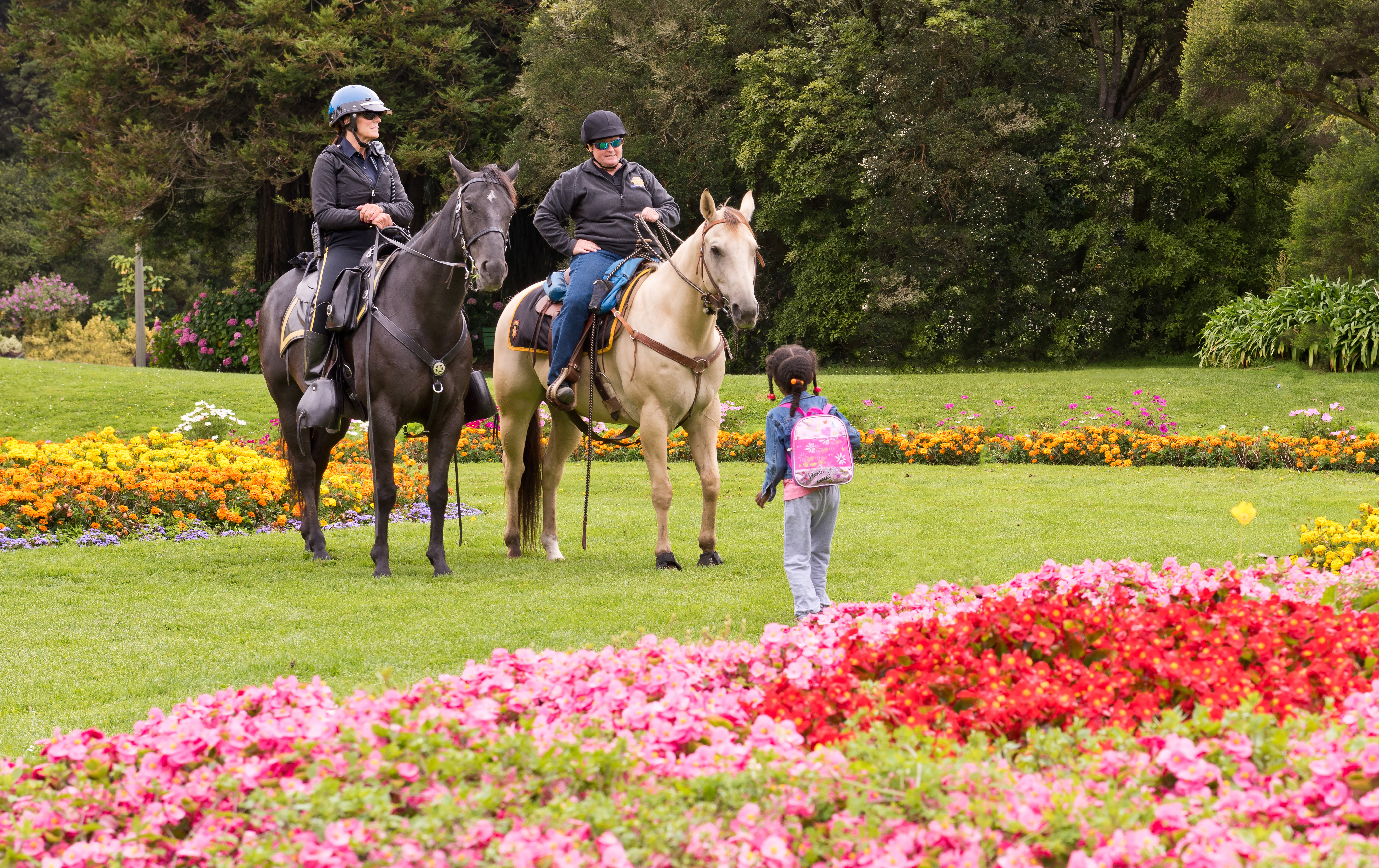 A little girl chats with police officers on horses in a green park.
