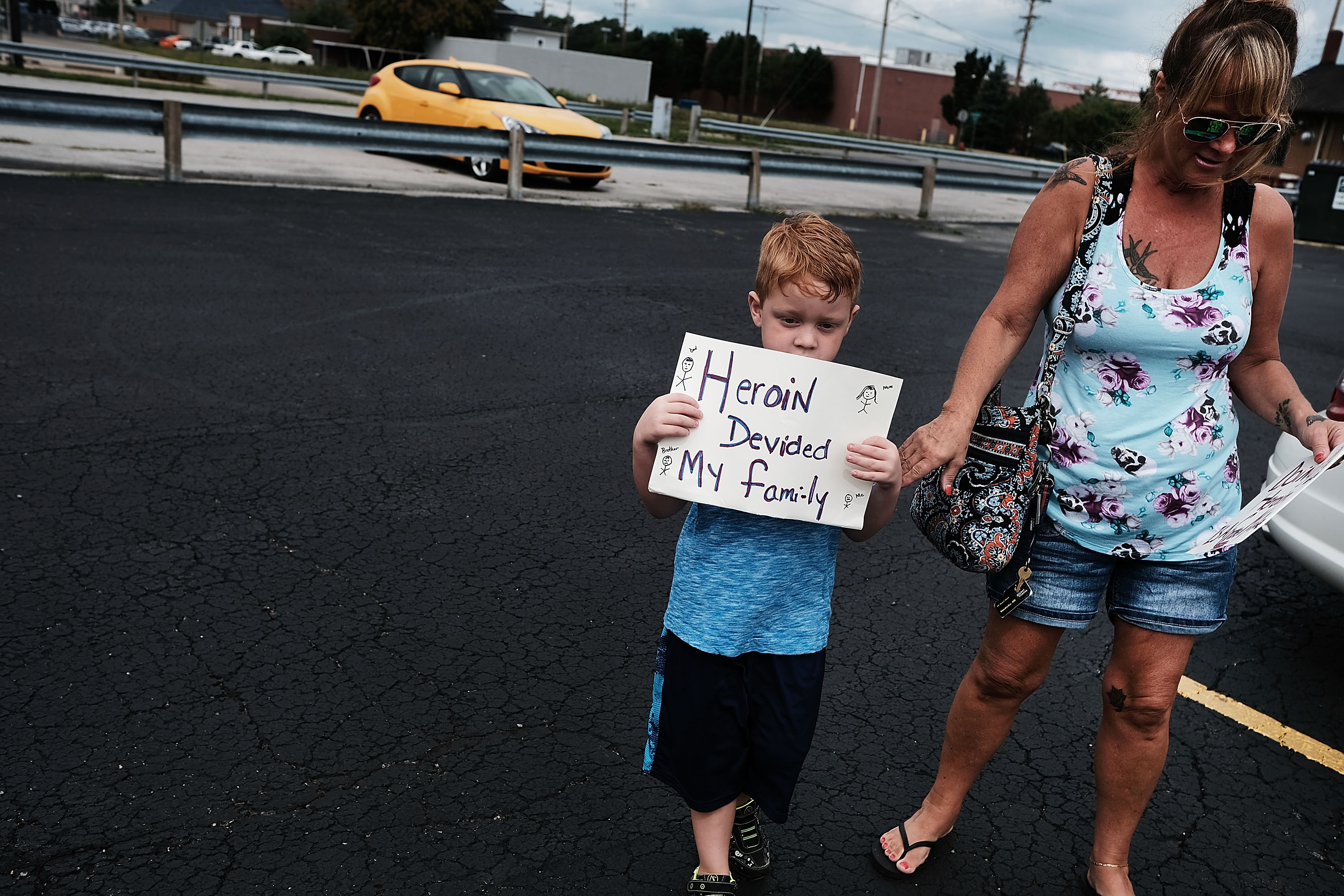 """A little boy stands with his mother on their way to join a march against the opioid epidemic. He holds a sign that reads, """"Heroin destroyed my family."""""""