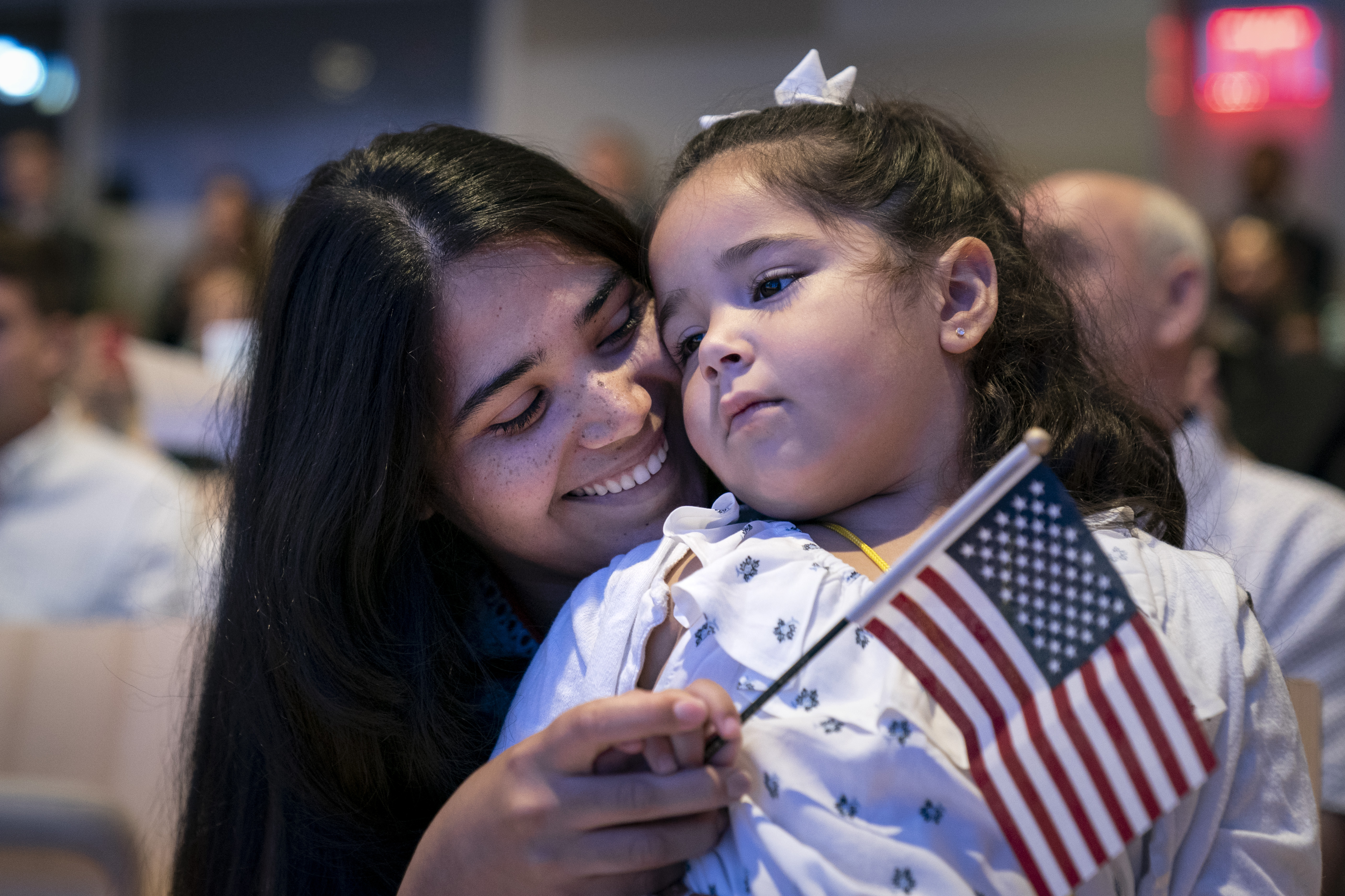 A smiling young woman holds her daughter on her lap and a small American flag in her hand.