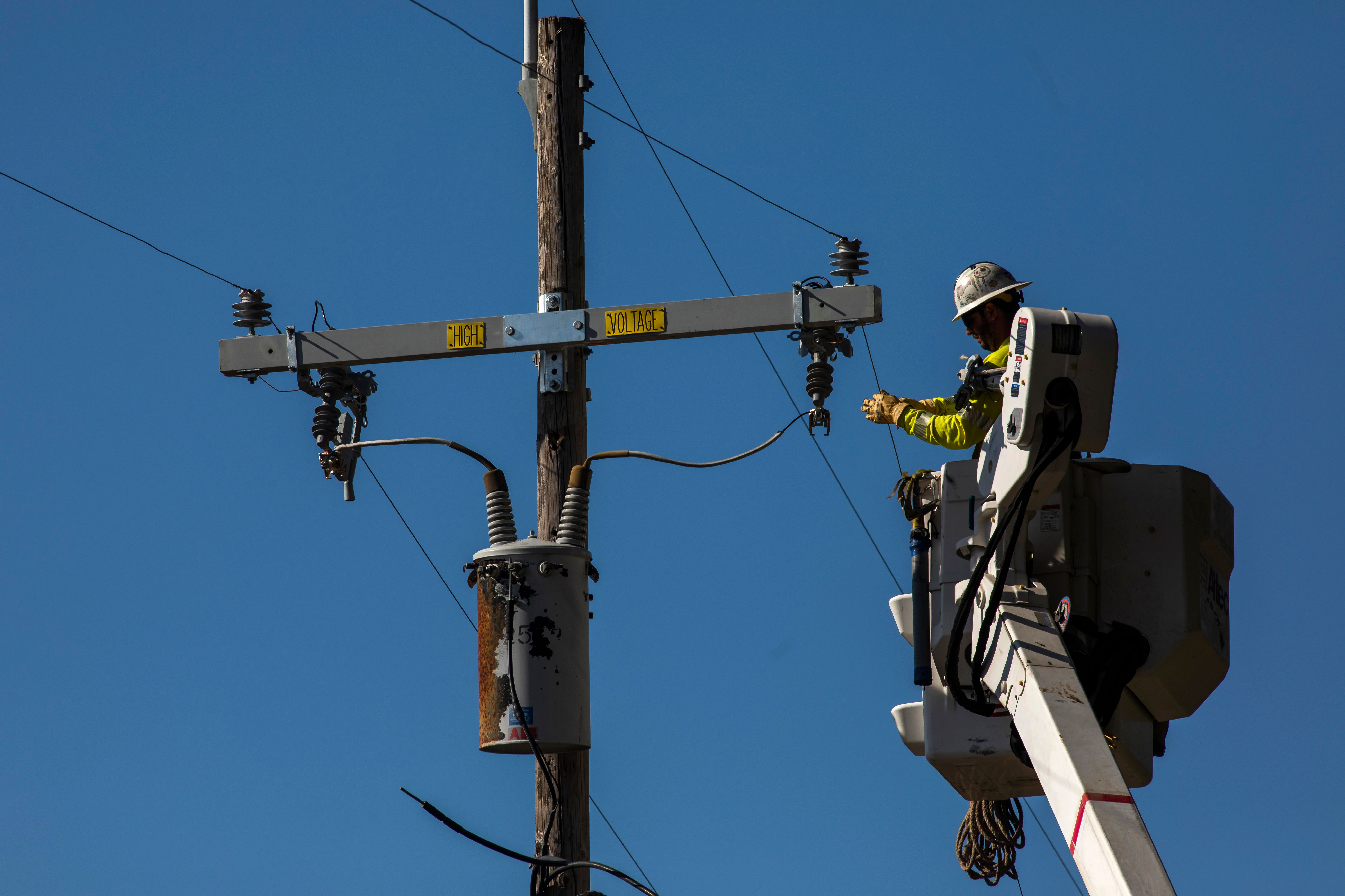 A worker in a hardhat and yellow vest using a crane to reach power lines during an inspection.