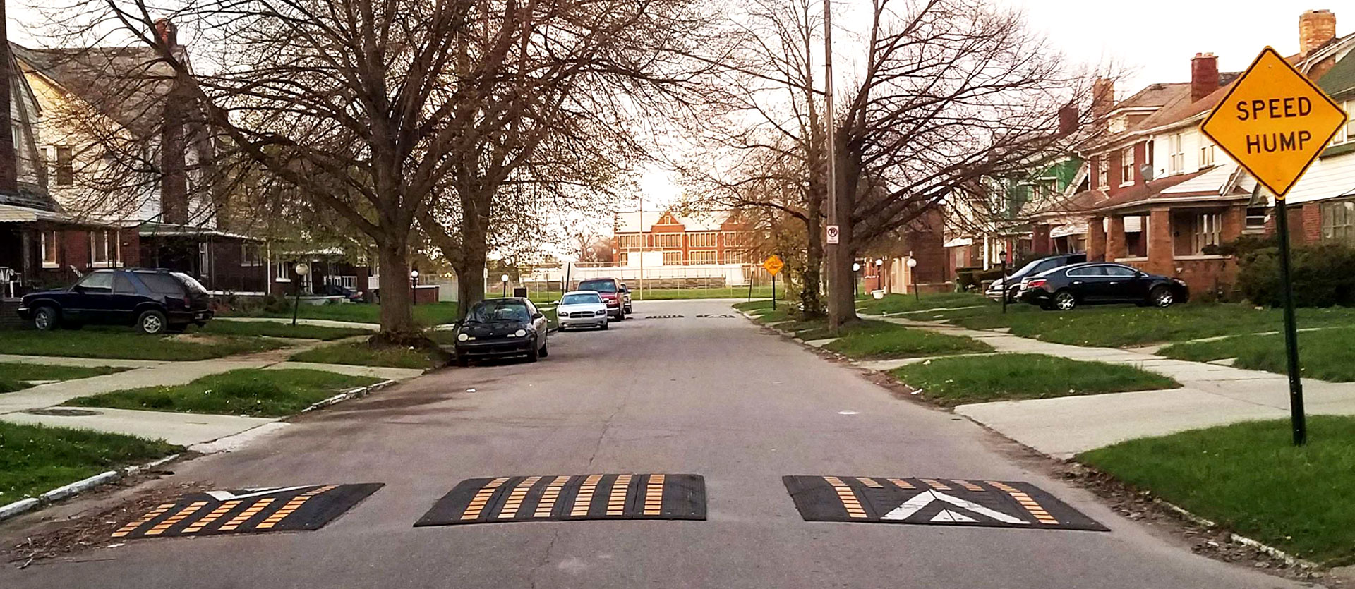 Three rubber speed cushions in a single line on a residential street.