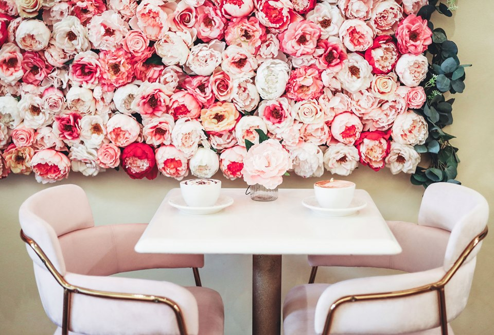A pink flower packed wall installation over a pink table with two pink and gold chairs. On the table are two cappuccino cups topped with swirled foam.