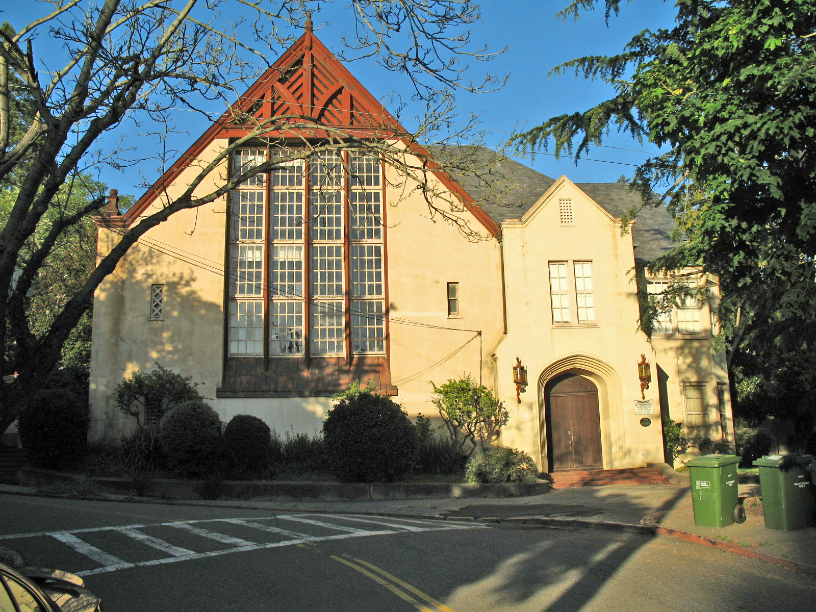 A Tudor building with a white facade, red eaves, and high arched roof.