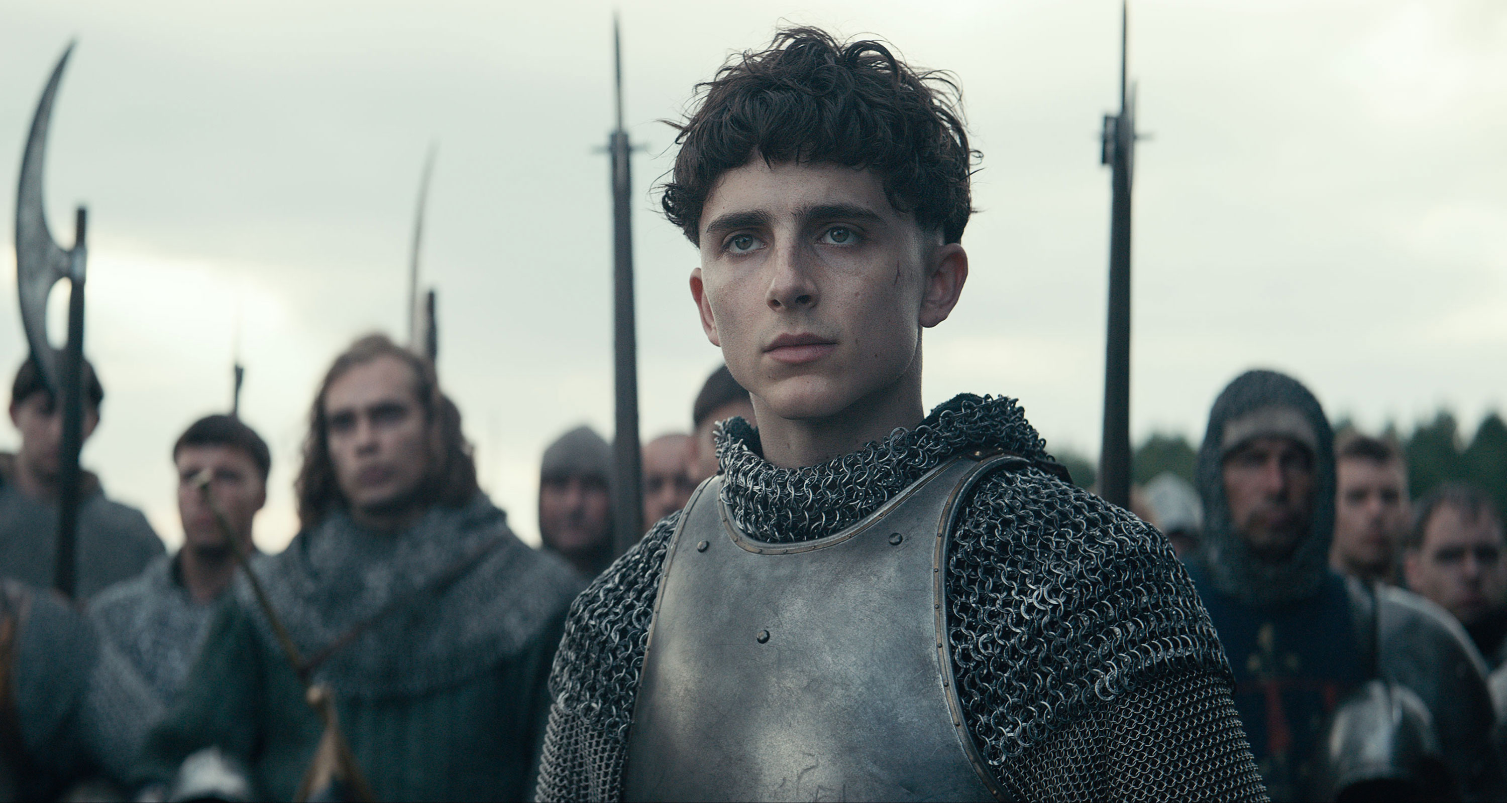 Henry (Chalamet), clad in armor, looks thoughtful.