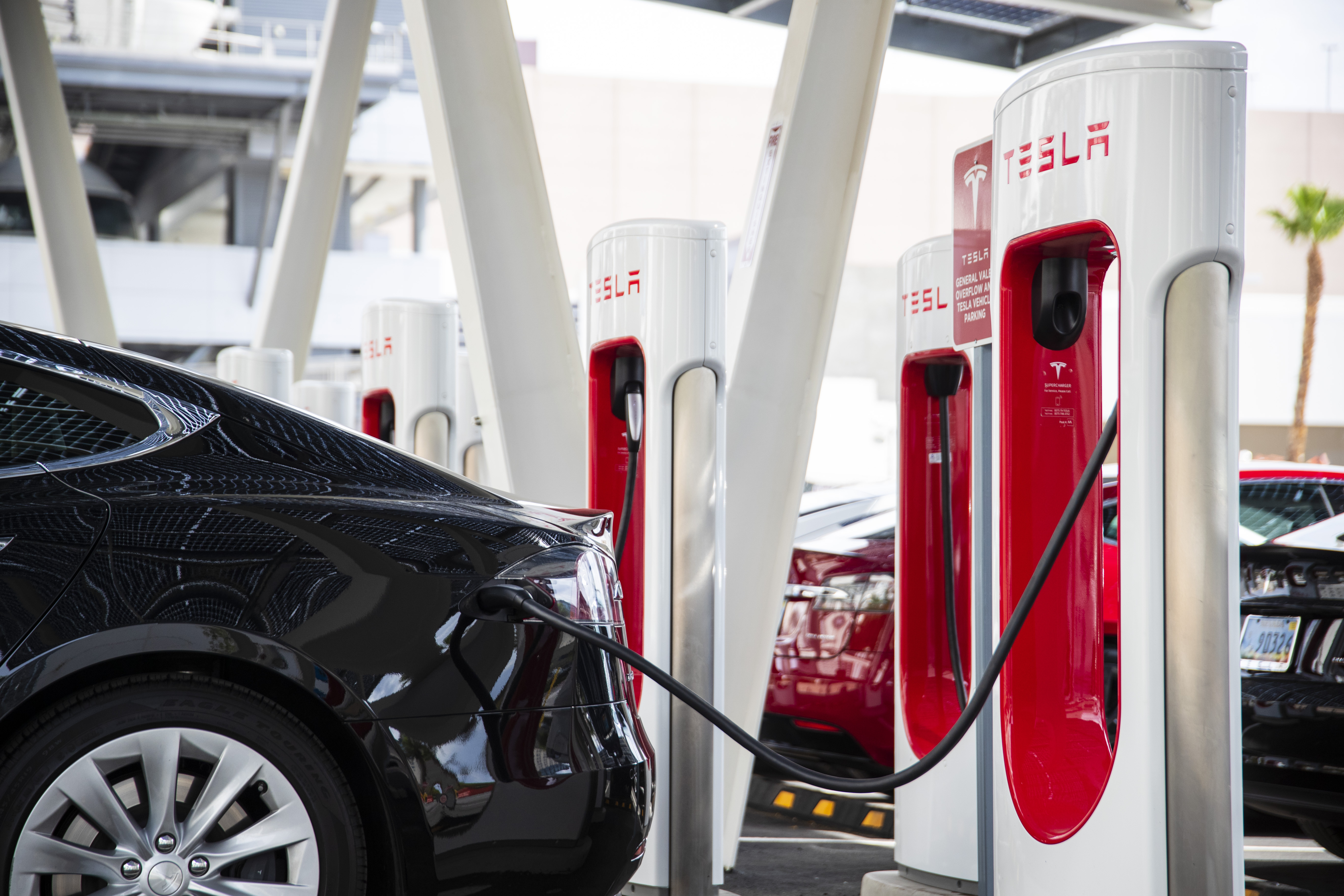 A Tesla vehicle is plugged in at a Tesla Supercharger station in Las Vegas.