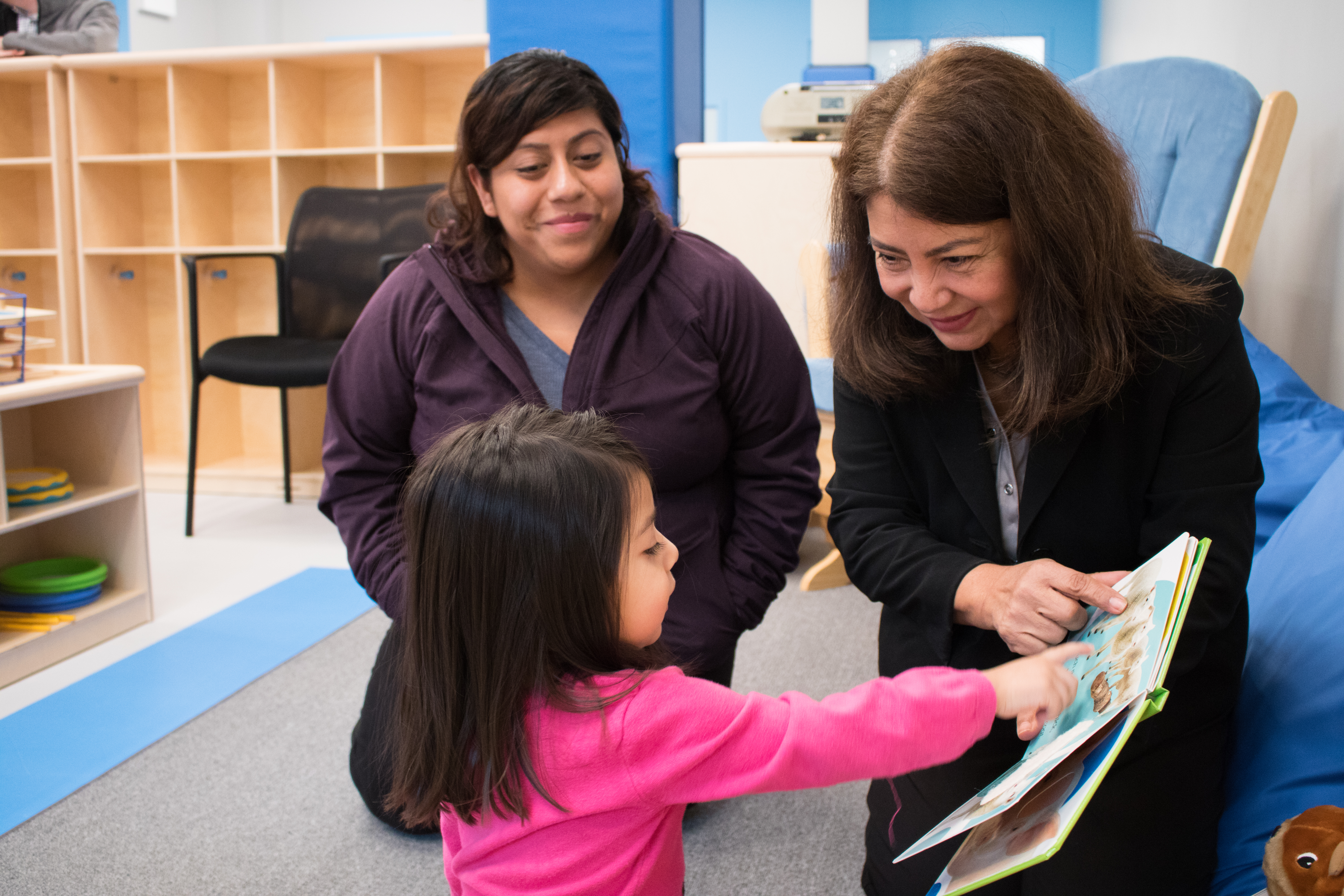 Maricela García (right) reads to Yennya Segura's (left) daughter in Gads Hill Center's new $7 million facility in Brighton Park.