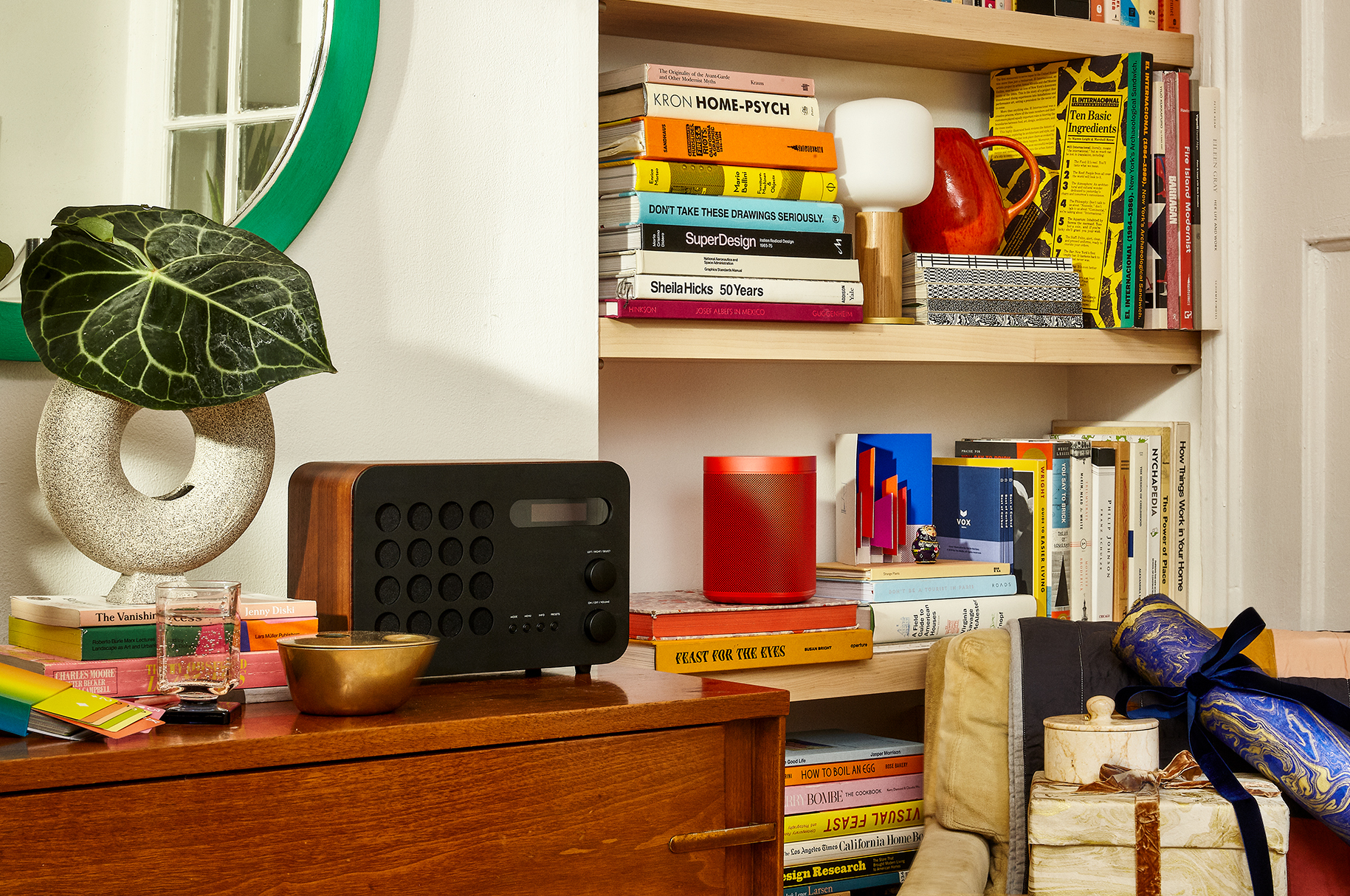 Multiple books and objects, like a speaker and lamp, line wooden shelves. A radio sits on top op of a wooden dresser with a mirror hung right above.