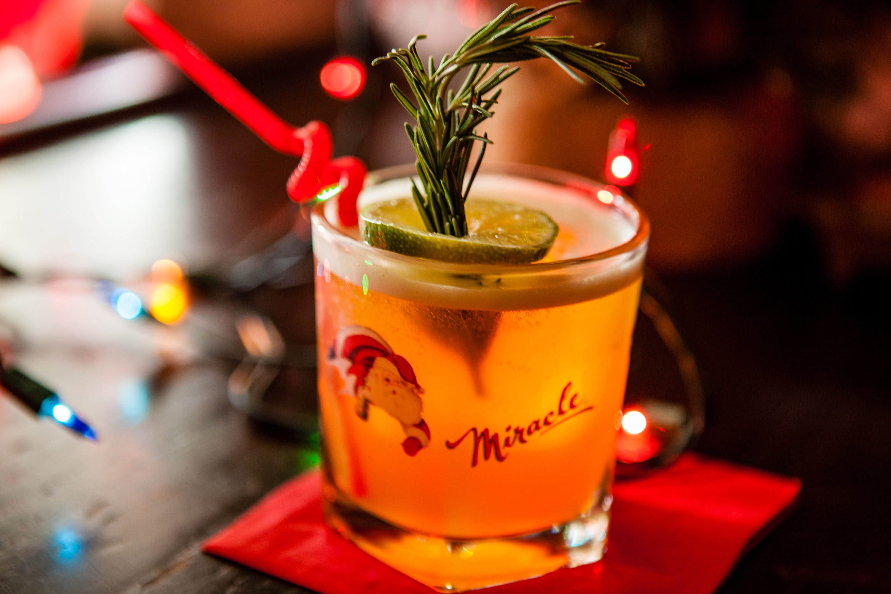 A Christmas-themed cocktail garnished with rosemary and lime