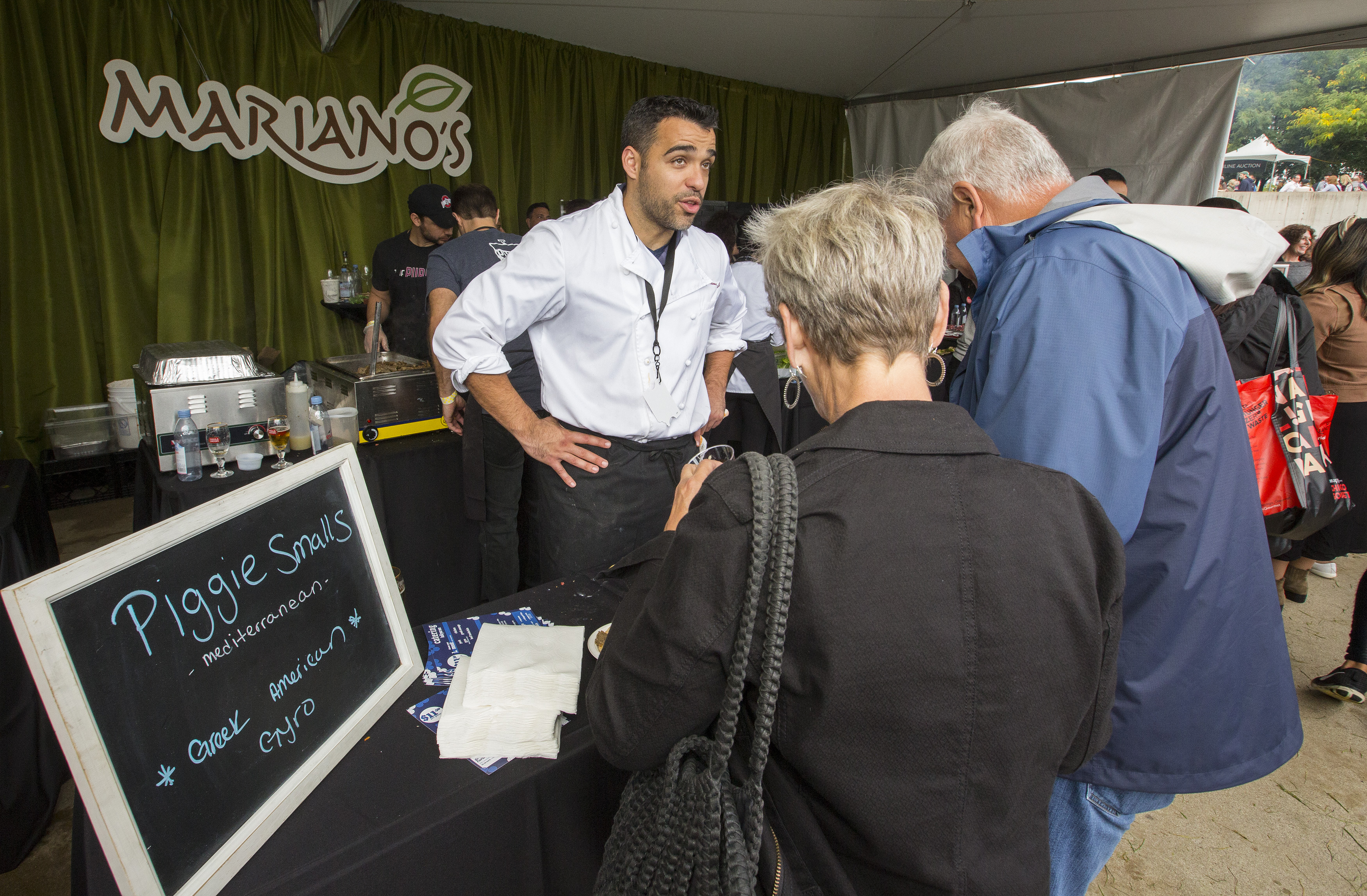 A man in a white shirt stands at a food stall at an event and talks to customers.