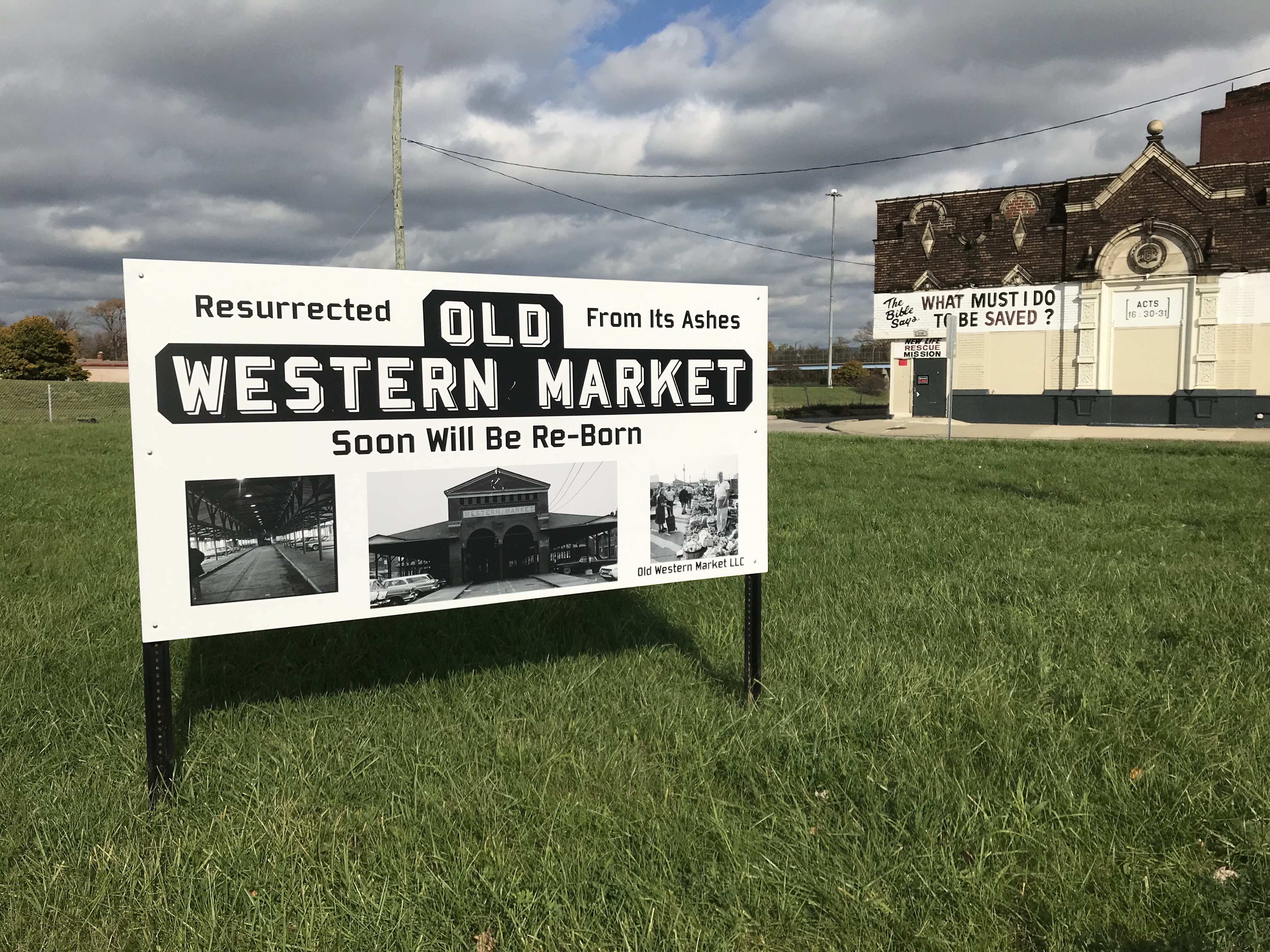 """A sign in a grassy lot with photos of an old brick, open-air market  that says """"Old Western Market."""""""