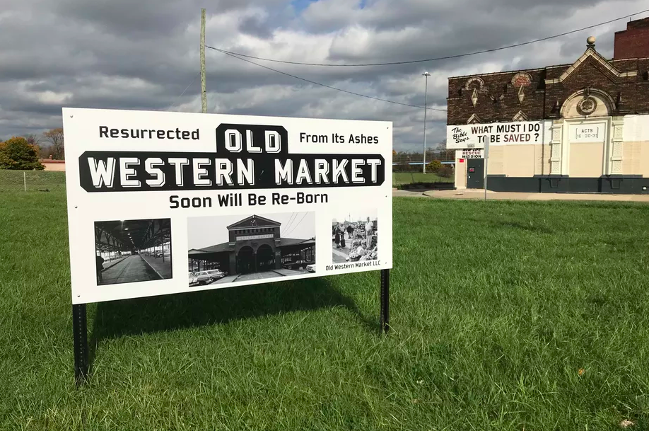 A  black and white sign for old western market in a grassy field next to the rescue mission