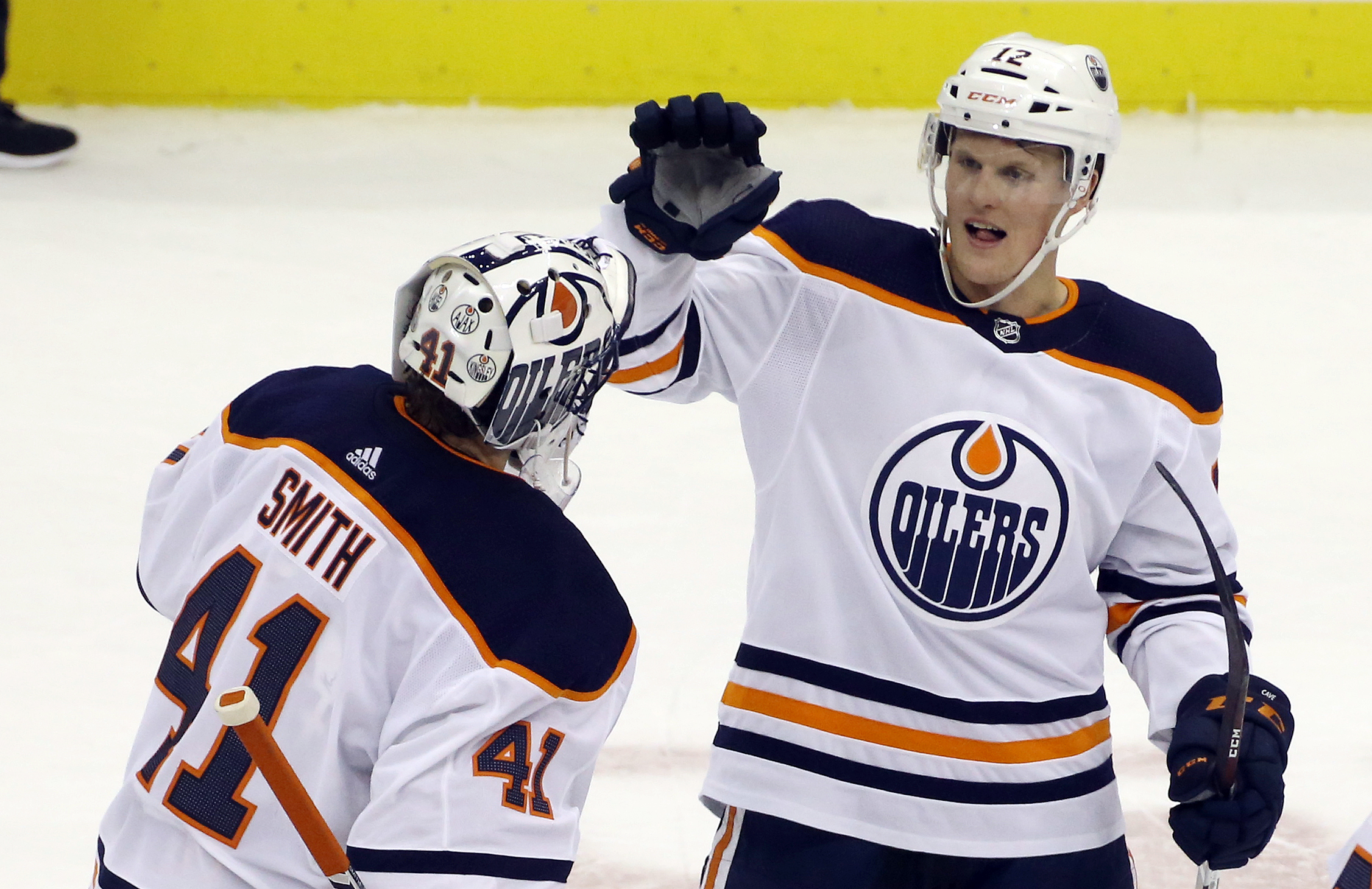 Edmonton Oilers goaltender Mike Smith (41) and center Colby Cave (12) celebrate after defeating the Pittsburgh Penguins at PPG PAINTS Arena. The Oilers won 2-1 in overtime.