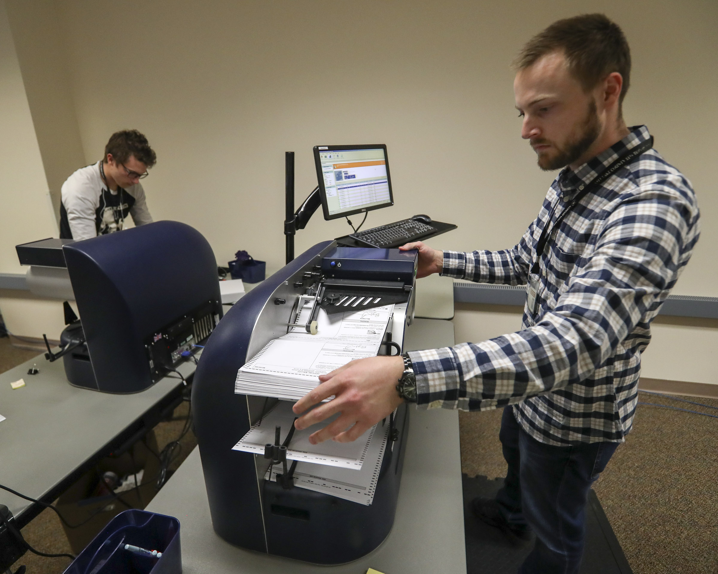 Salt Lake County data analyst Stephen Moore, right, and Spencer Dillon, a temporary employee, tabulate ballots at the Salt Lake County Government Center in Salt Lake City on Monday, Nov. 4, 2019.