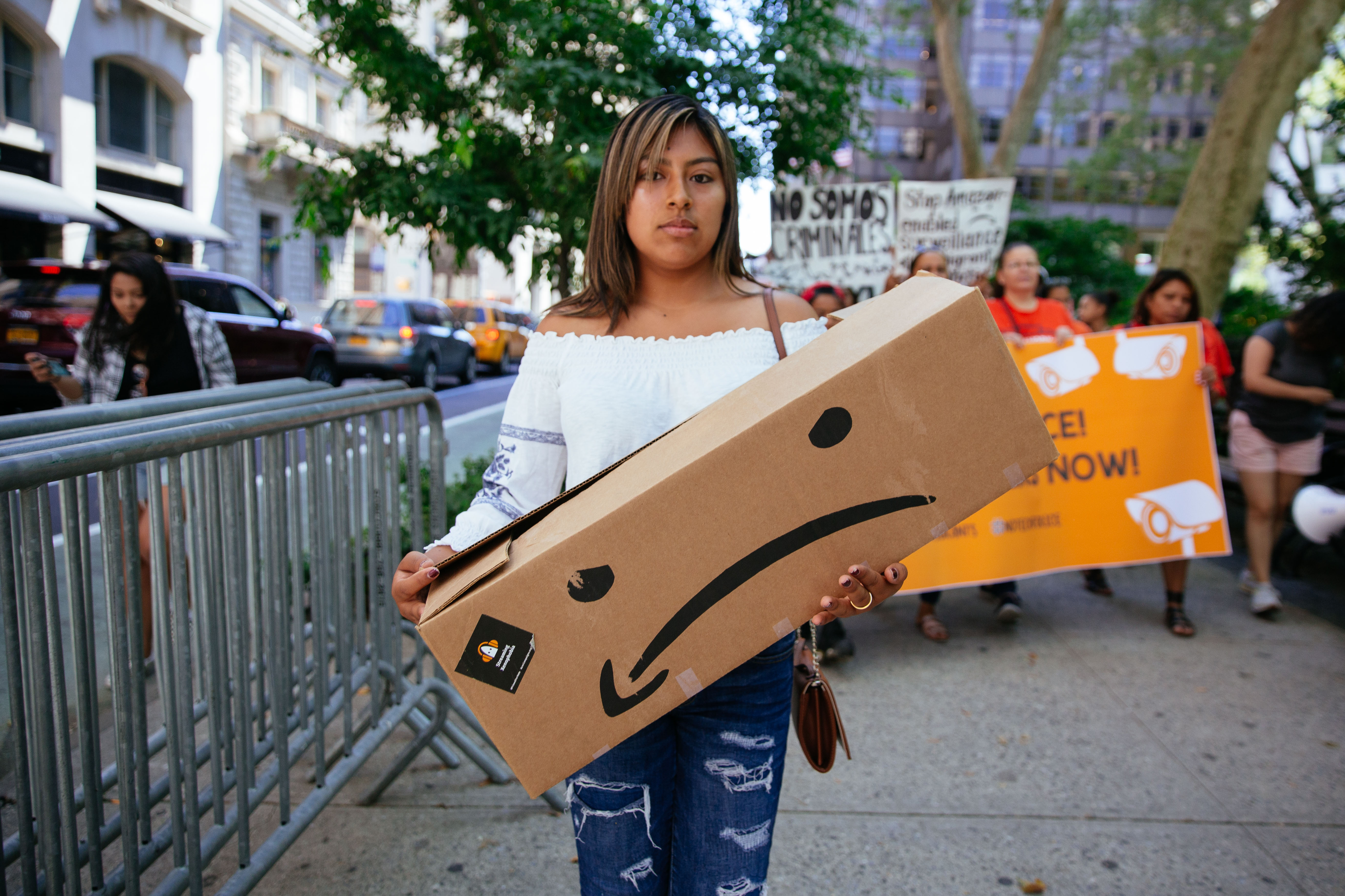 A protester holds an Amazon box made into a sad face as part of a protest against the company's cloud services contracts with Palantir, which supports ICE.