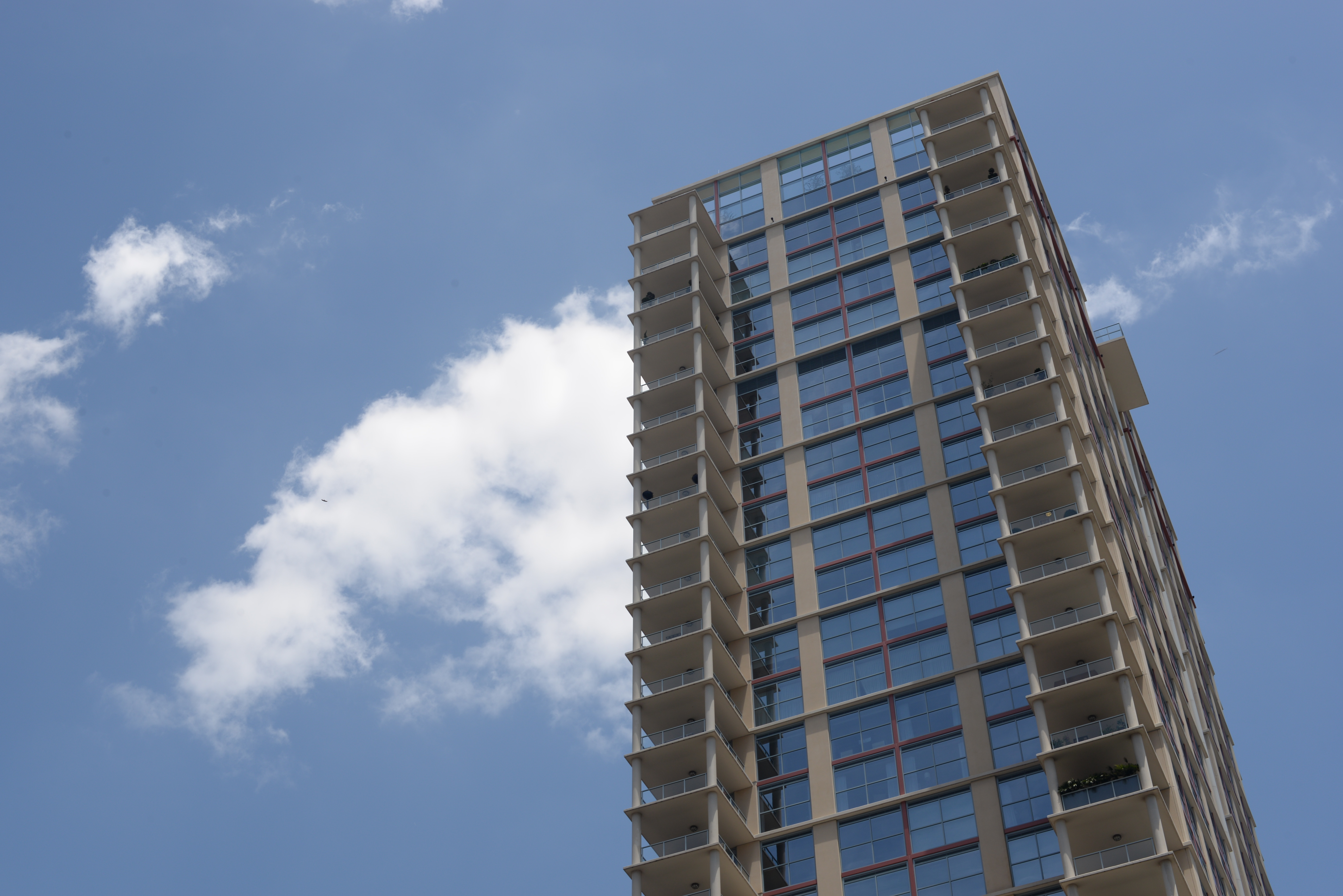 The top of a high-rise apartment building set against a cloudless blue sky.