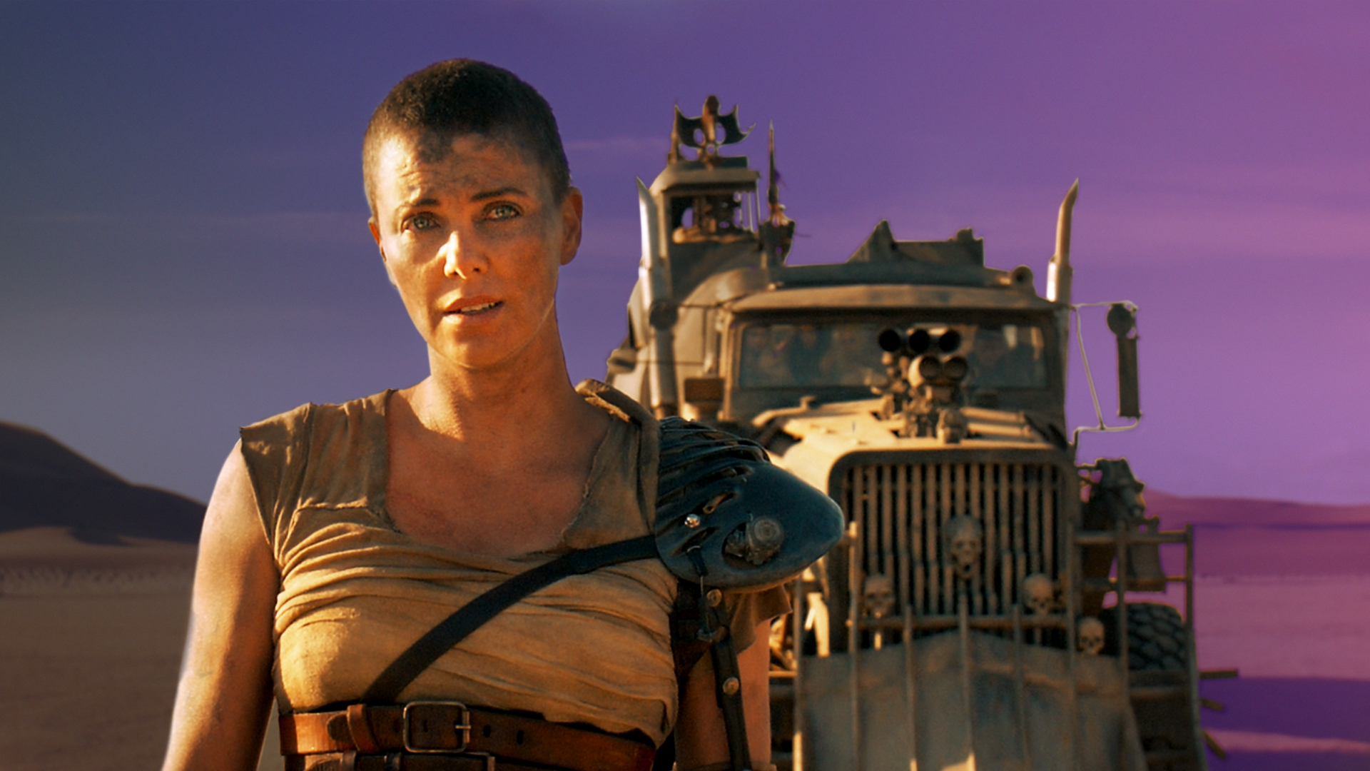 Charlize Theron stands in front of a post-apocalyptic truck in the movie Mad Max: Fury Road