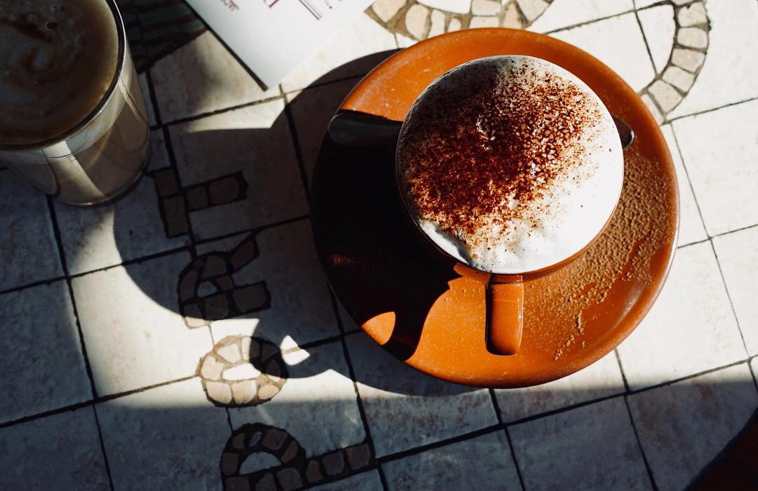 A cappuccino with chocolate on top on a tiled counter.