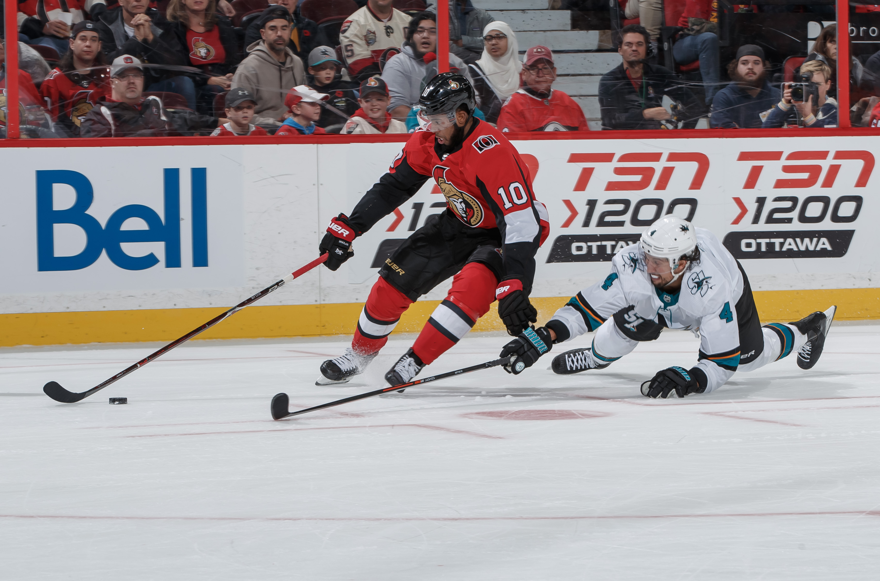 Anthony Duclair #10 of the Ottawa Senators stickhandles the puck against a sprawling Brenden Dillon #4 of the San Jose Sharks, leading to his third period goal at Canadian Tire Centre on October 27, 2019 in Ottawa, Ontario, Canada.