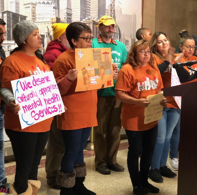 Estela Diaz speaking at a City Hall news conference Tuesday. She said she has struggled with depression and panic attacks since childhood, and attempted suicide while waiting five years for an appointment at a private clinic.