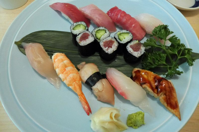 An assortment of raw fish and six pieces of sushi next to ginger and wasabi