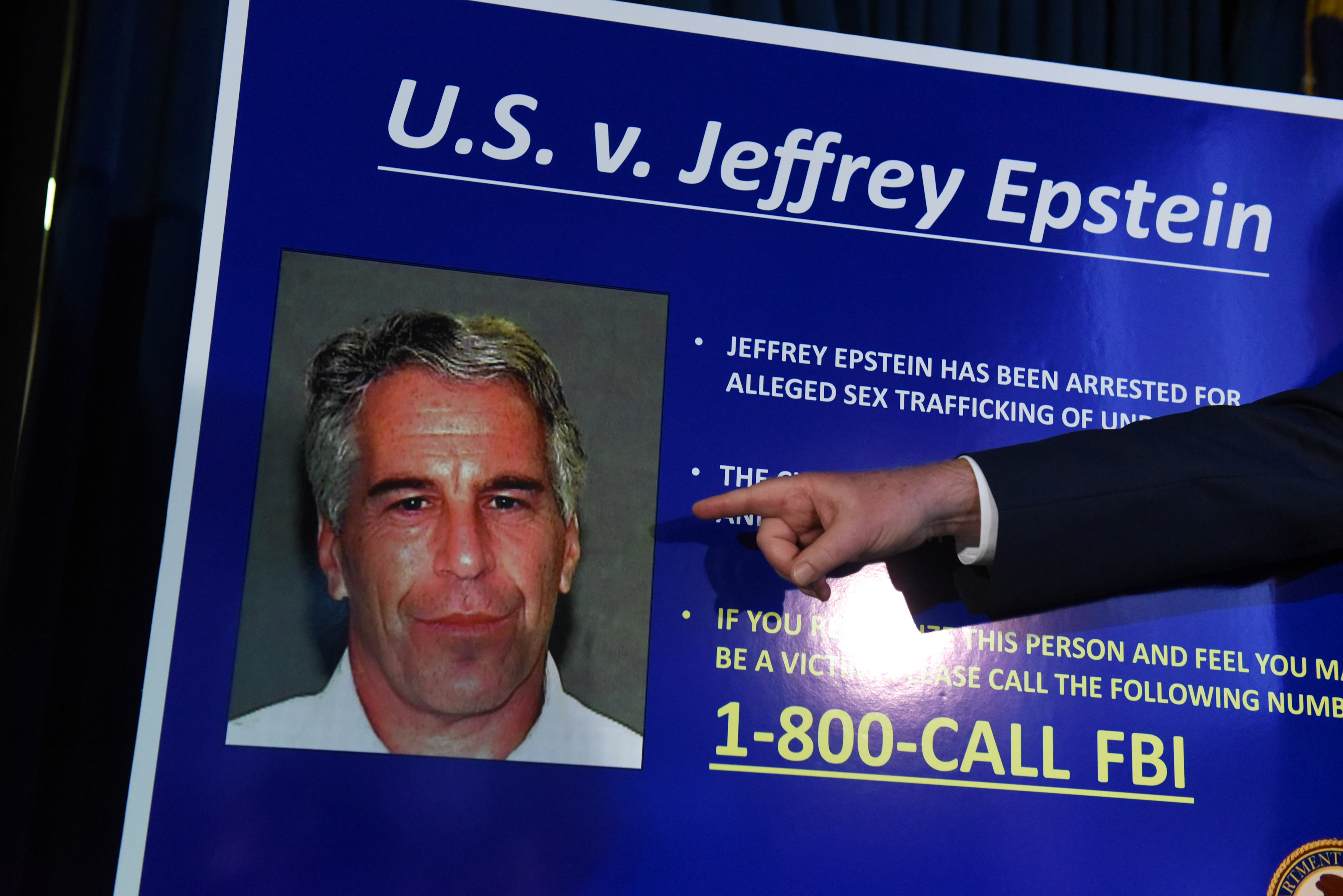 A disembodied arm points to a picture of Jeffrey Epstein during an announcement of charges being brought against him.