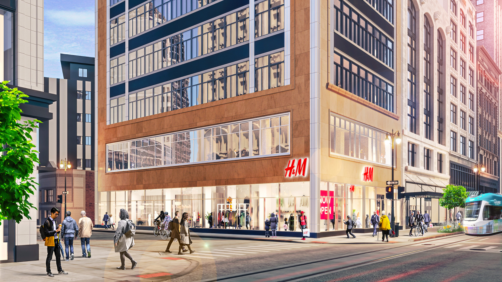 """A large building with a glass storefront and """"H&M"""" printed above the corner entrance. People walk around inside the store."""