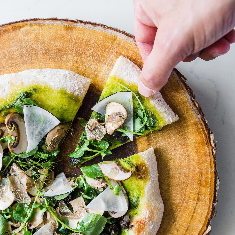 mushroom and pesto pizza on wood board