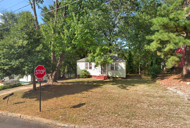 A yellow cottage set back on a brown lot near a stop sign in Atlanta.