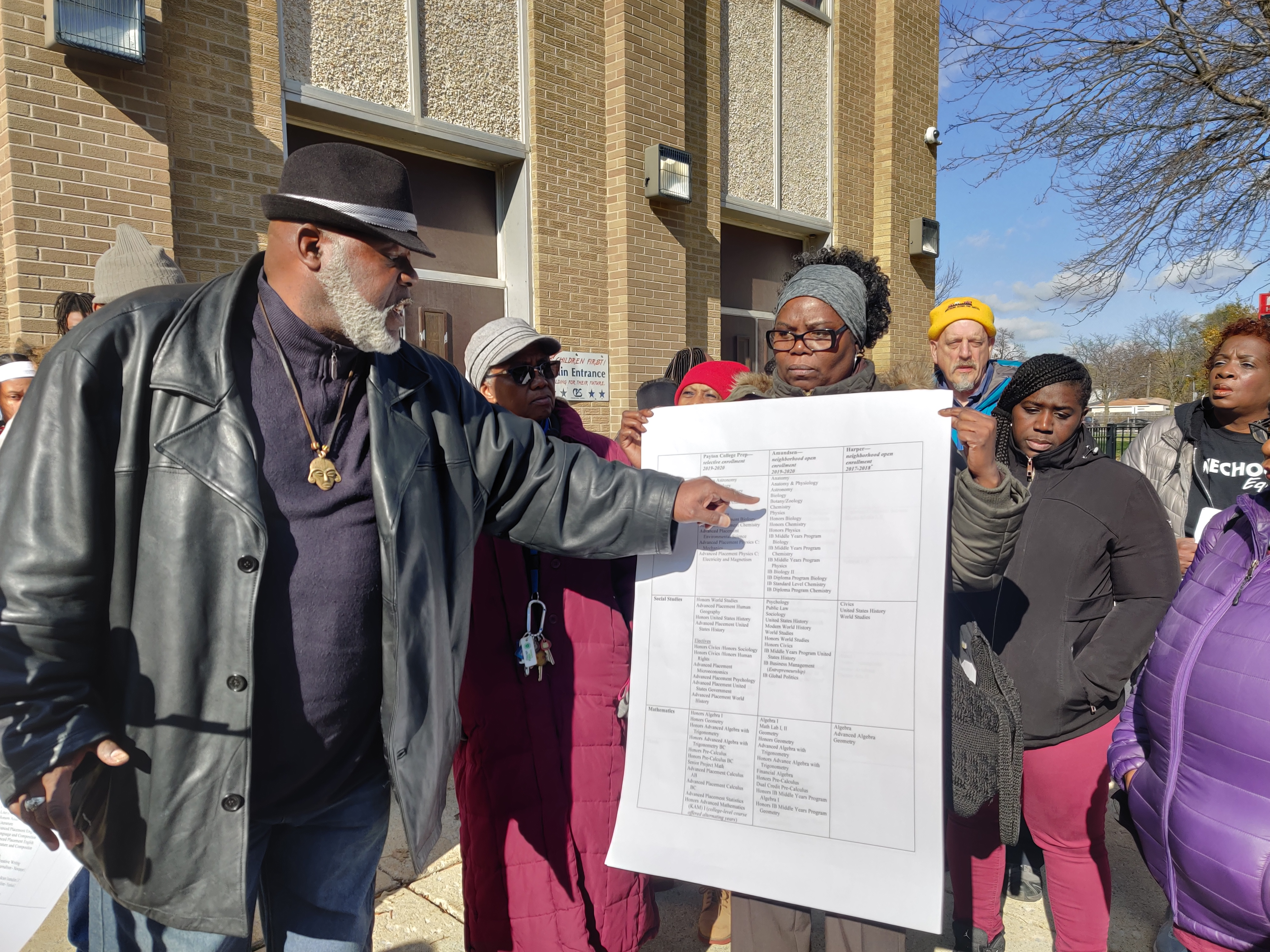 Jitu Brown points at a chart showing the disparities between Harper High School's curriculum and two other North Side high schools.