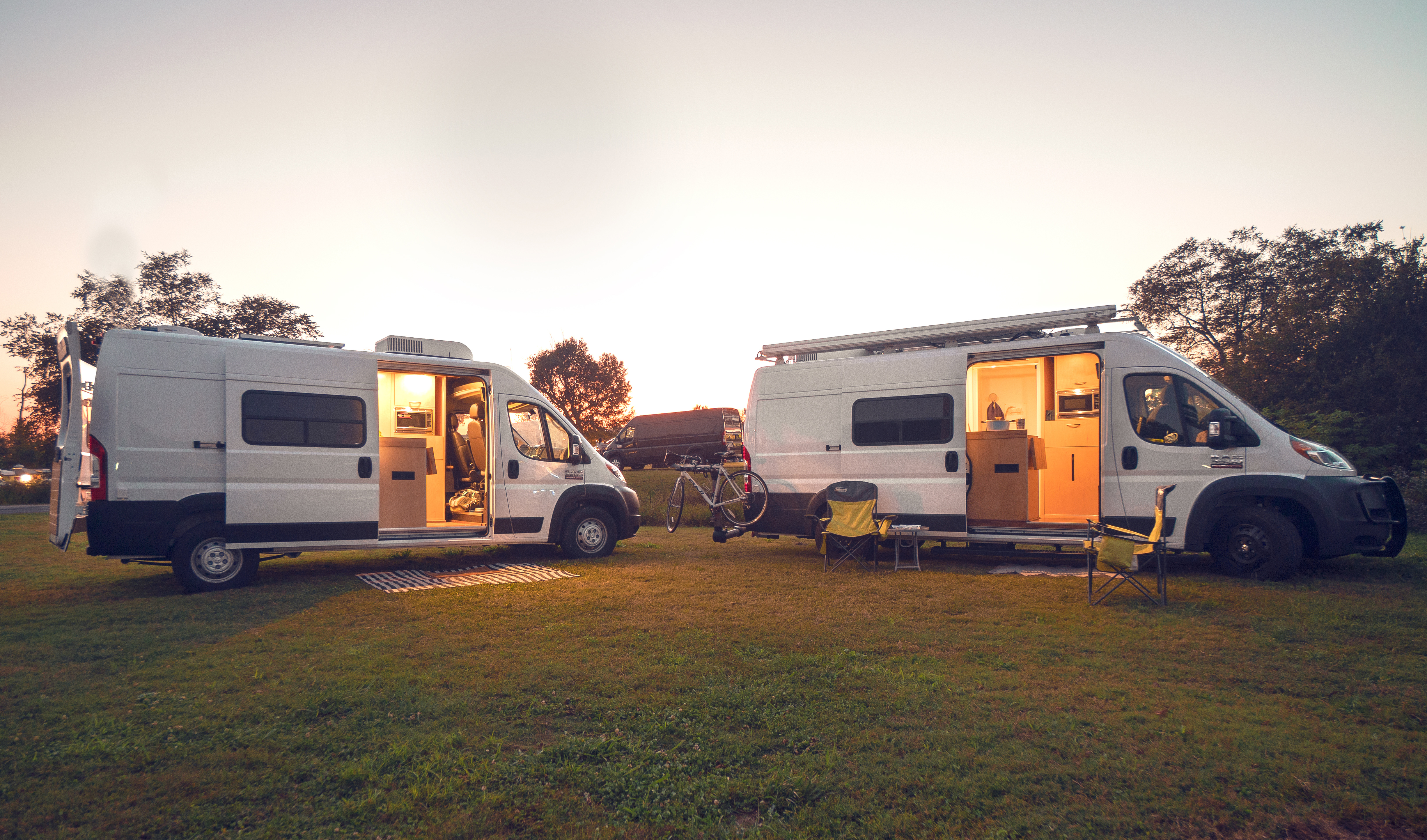 Two white camper vans sit in a grassy area with trees in the background. It's sunset, so the van doors are open and you can see the light from within.