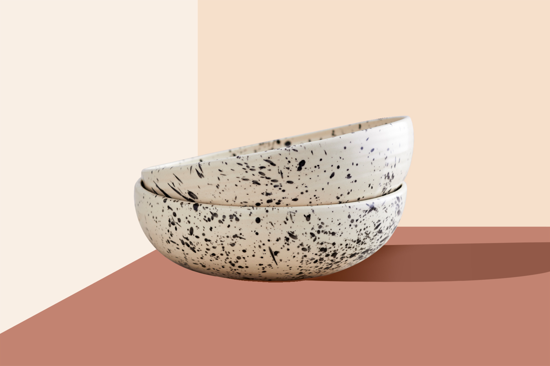 Two bowls with a black and white pattern are stacked and sitting on a background with a geometric color pattern.
