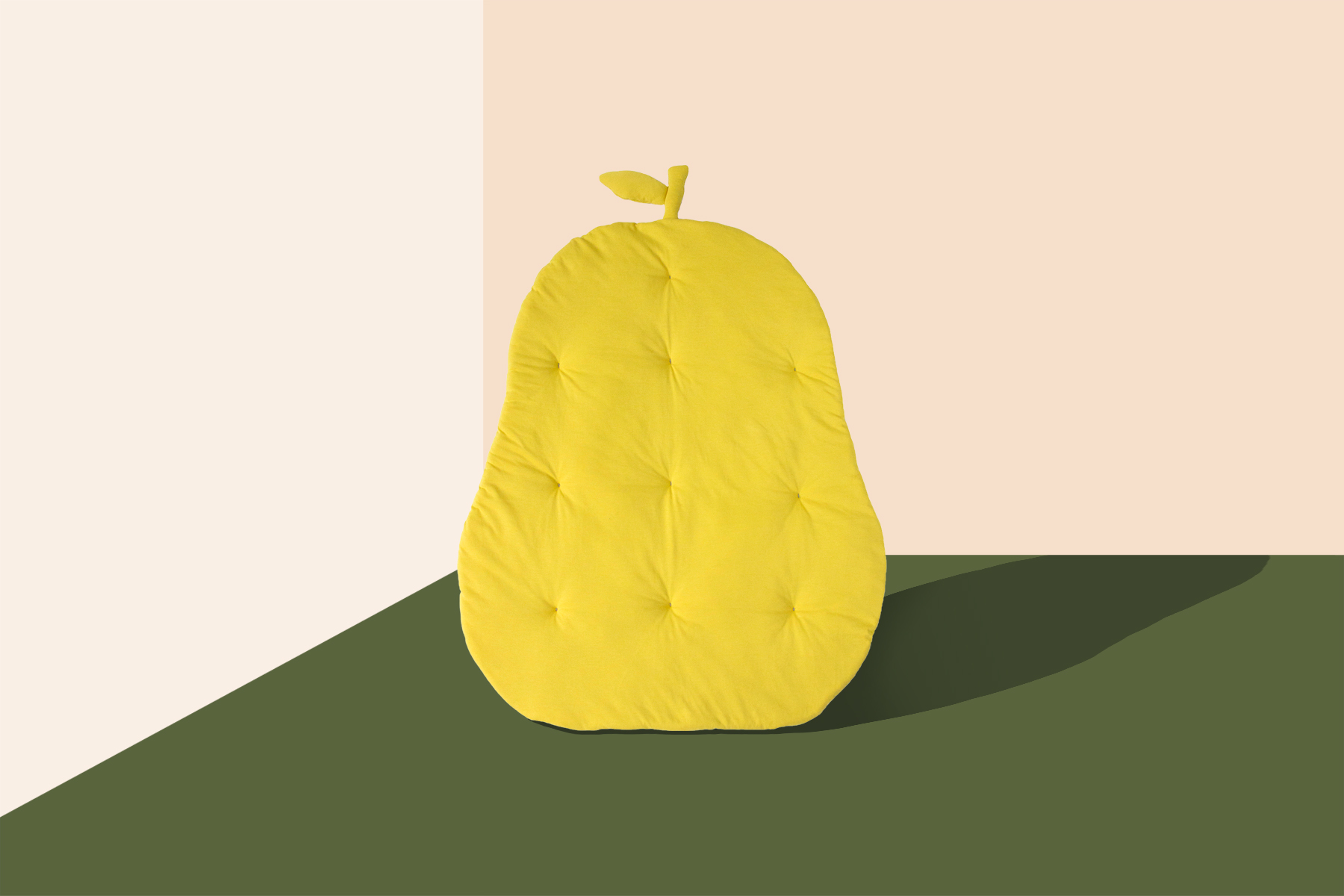 A green pear shaped soft cushion is on a background with a multicolored geometric pattern.