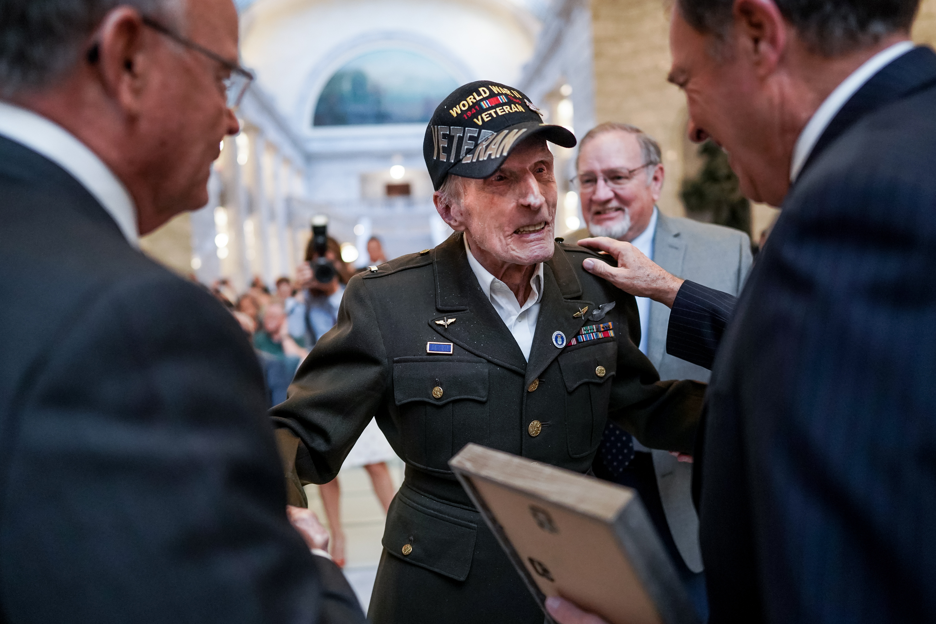 Dan Eastman, 99, greets Utah Senate President Stuart Adams, R-Layton, left, and Gov. Gary Herbert, right, during a ceremony honoring centenarian veterans at the Capitol in Salt Lake City on Tuesday, Nov. 5, 2019. Eastman, wearing his original uniform and accompanied by his son, Alan Eastman, back right, flew an A-20 medium bomber in the Army Air Corps during World War II.
