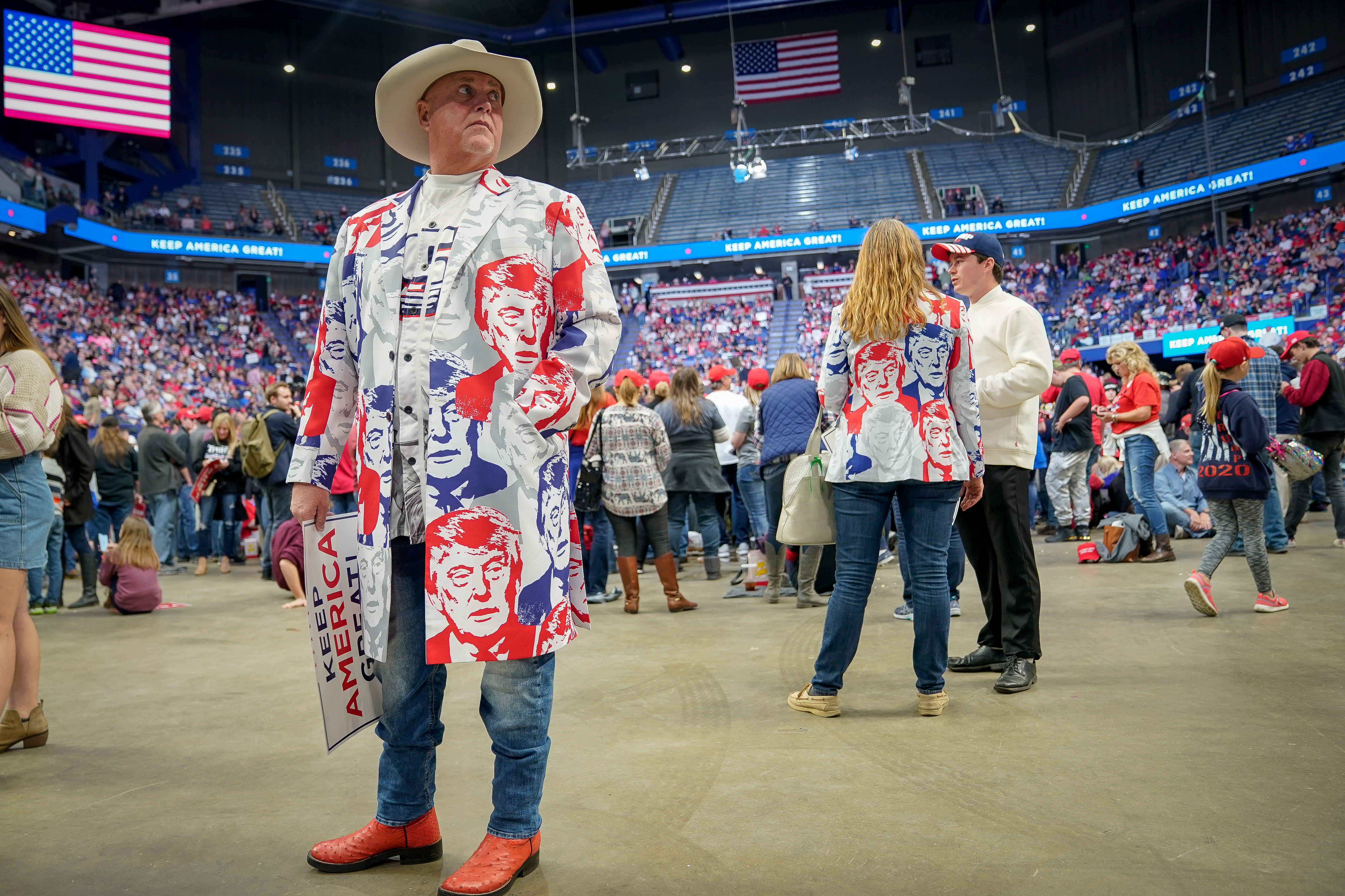 A man wearing a coat made of fabric imprinted with Donald Trump's face stands in an arena before a Donald Trump rally.