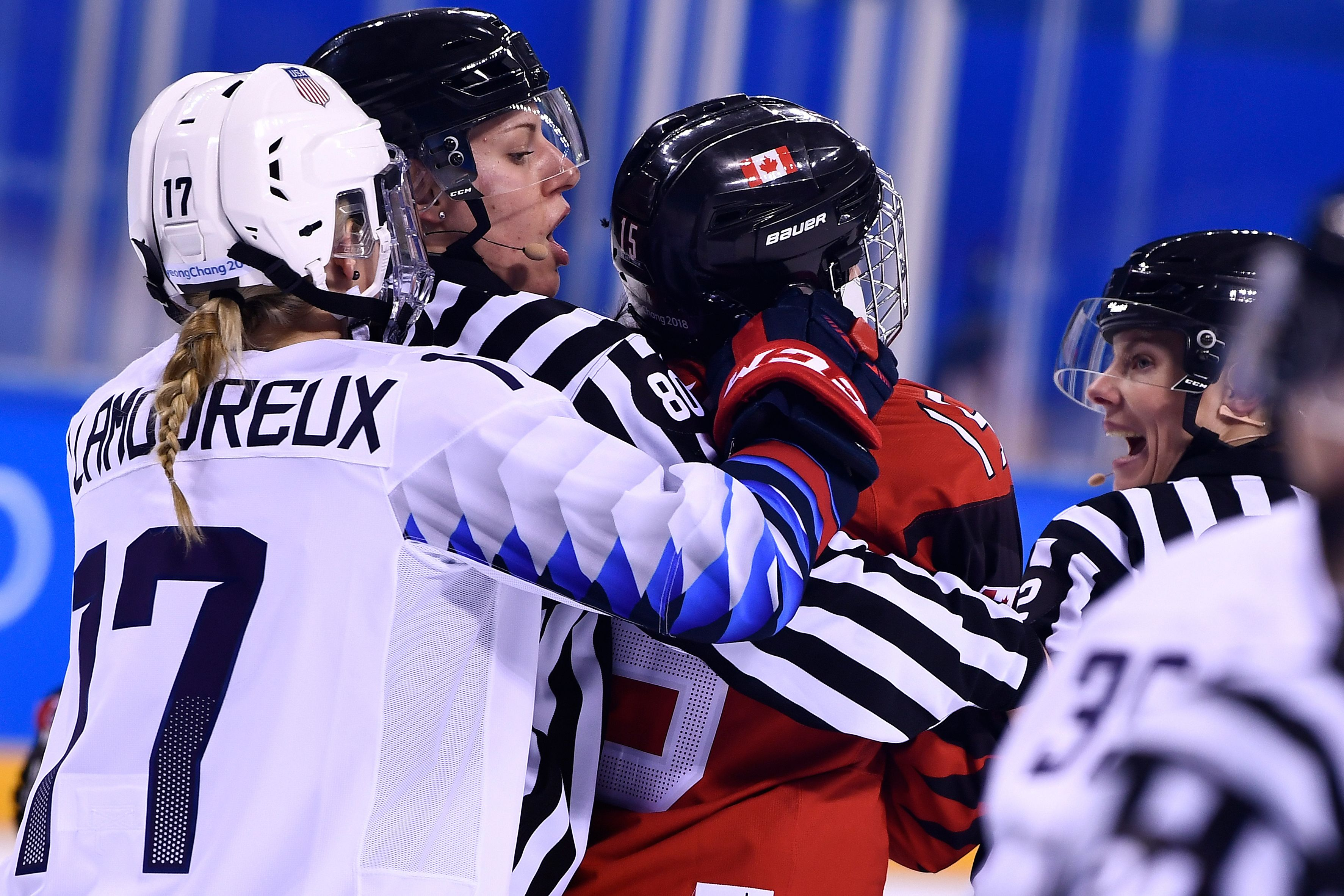 USA's Jocelyne Lamoureux-Davidson (L) pulls on Canada's Melodie Daoust's helmet in the women's preliminary round ice hockey match between the US and Canada during the Pyeongchang 2018 Winter Olympic Games