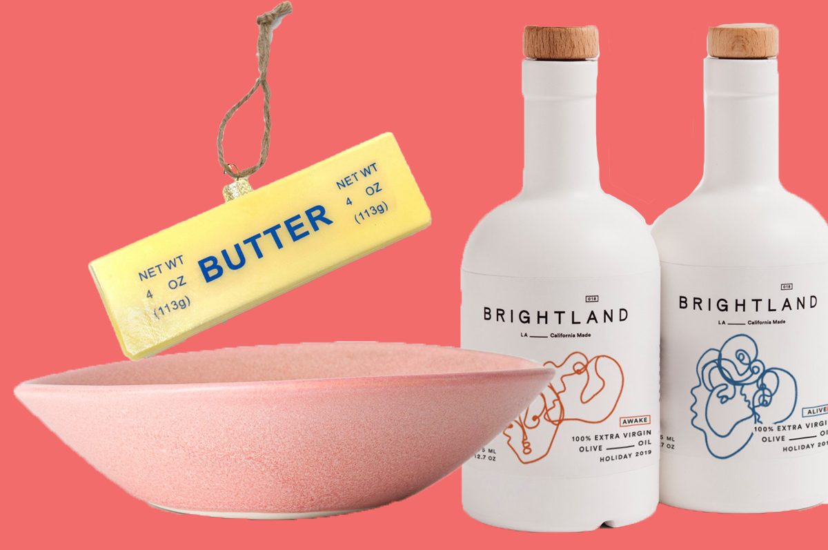 A stick of butter Christmas tree ornament, a pastel pink wide pasta bowl, and two white bottles of stylish-looking olive oil, all on a pink background