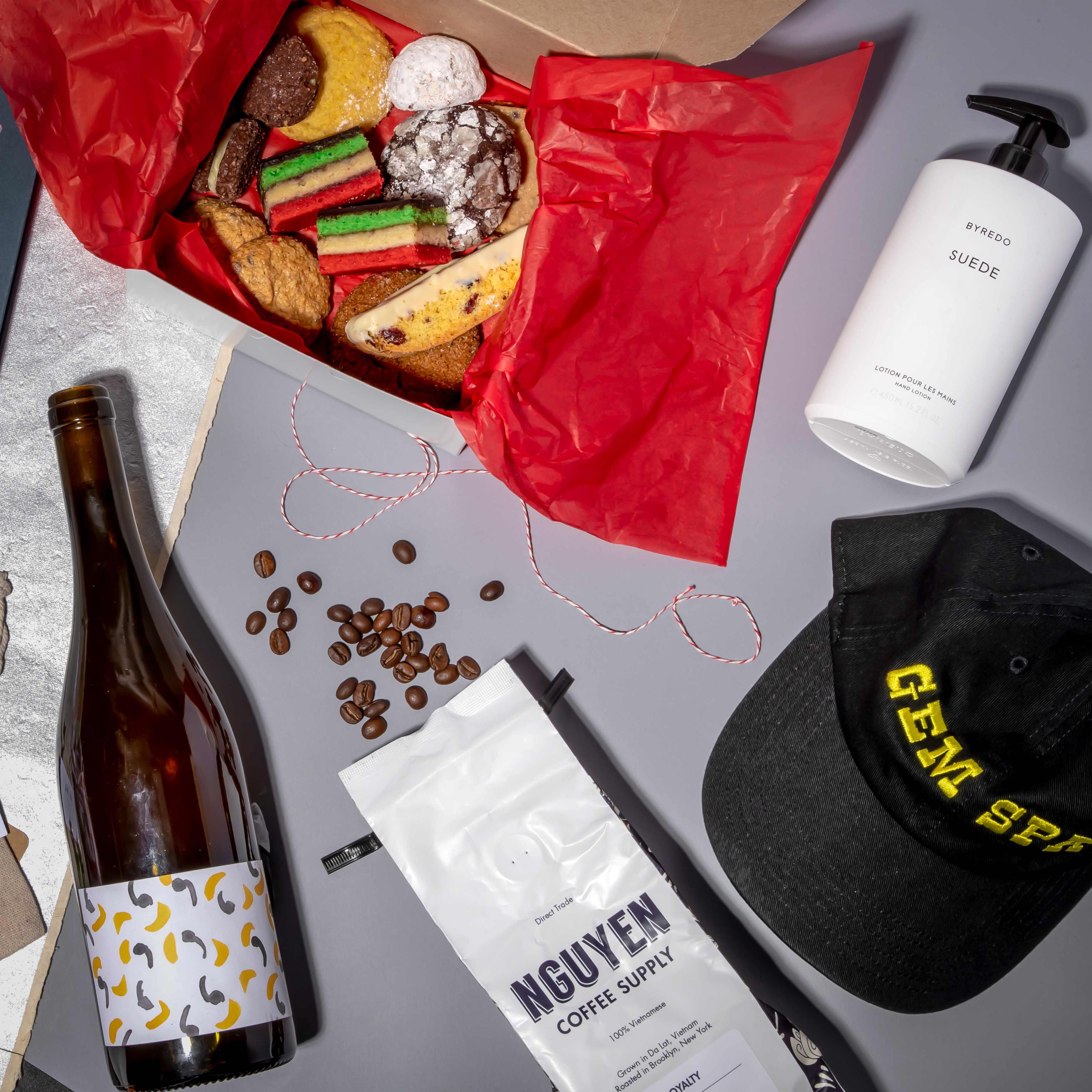 """Various gifts arranged together, including colorful assorted cookies, a white bottle of hand lotion, a black hat saying """"Gem Spa,"""" and a bag of coffee"""