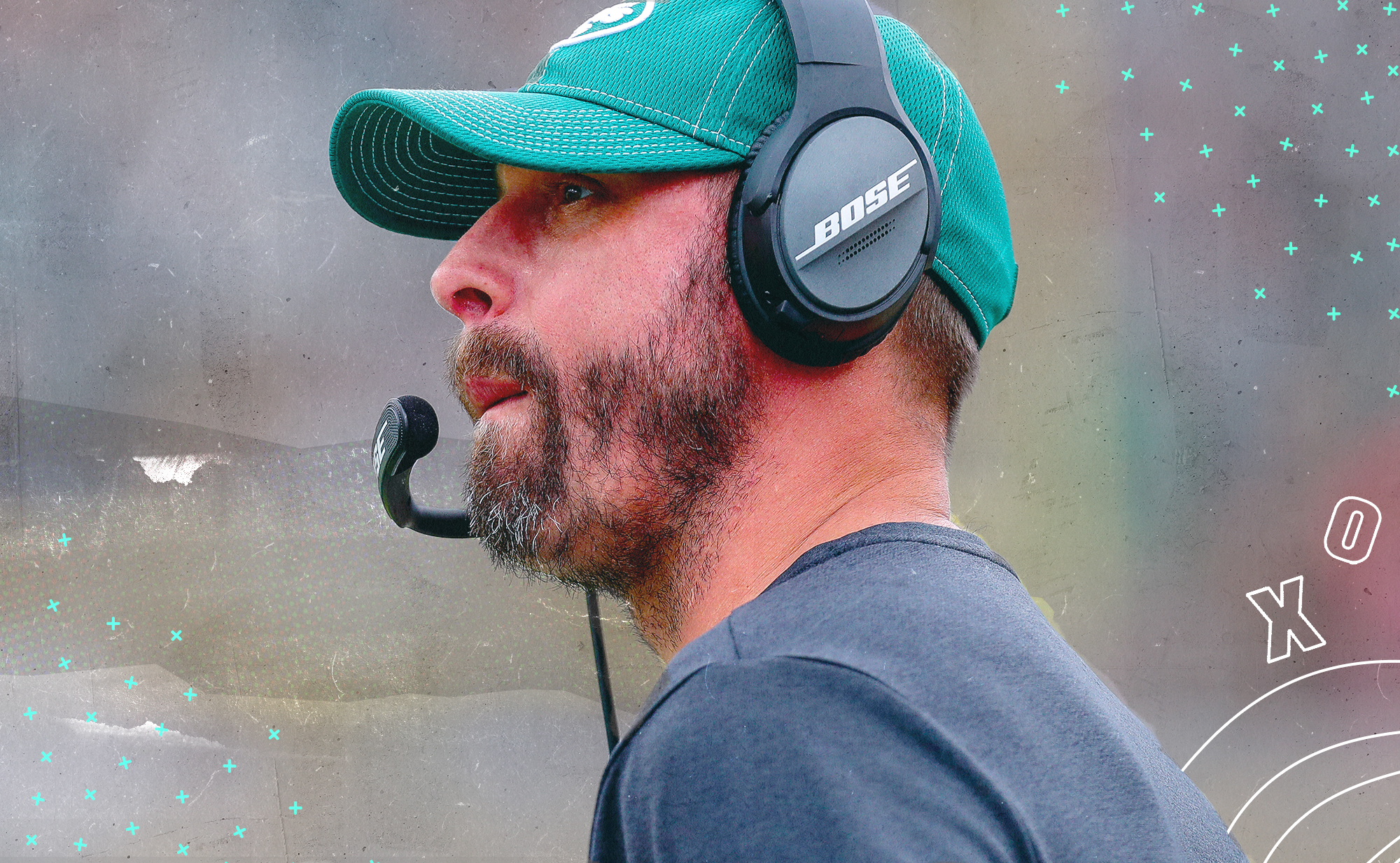 Jets head coach Adam Gase, wearing his headset, in front of a background with white Xs and Os