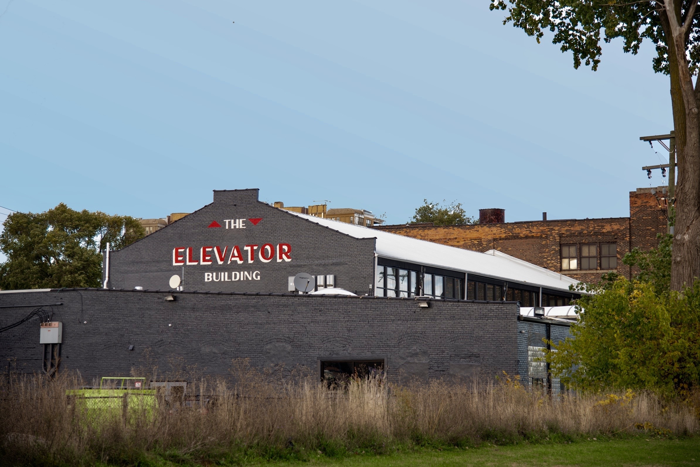 """A gray-painted industrial building with a logo, painted in red and white, that says """"The Elevator Building."""""""