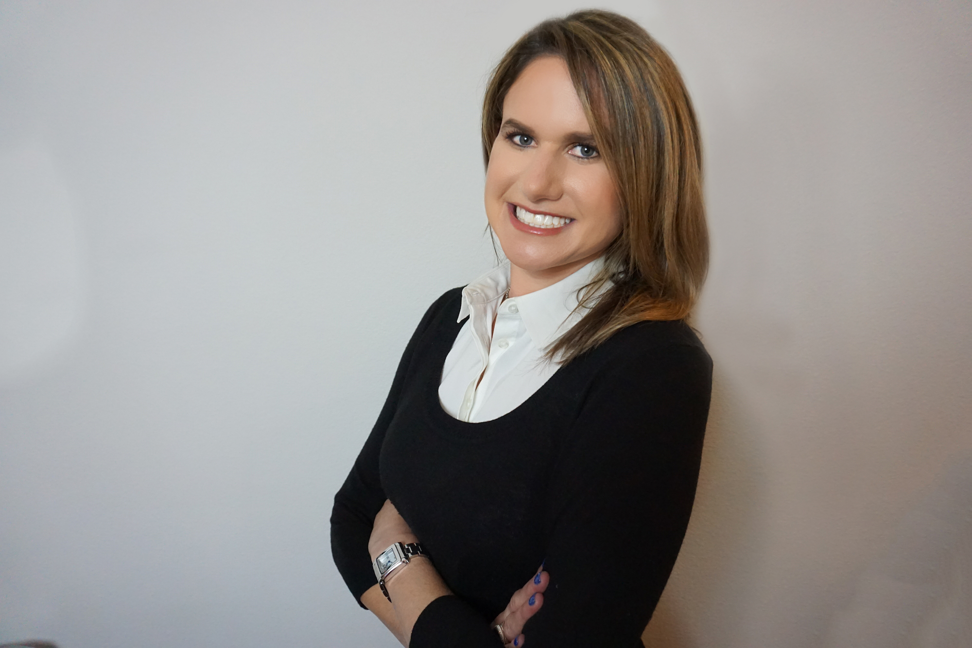 A woman in a black sweater with her arms crossed