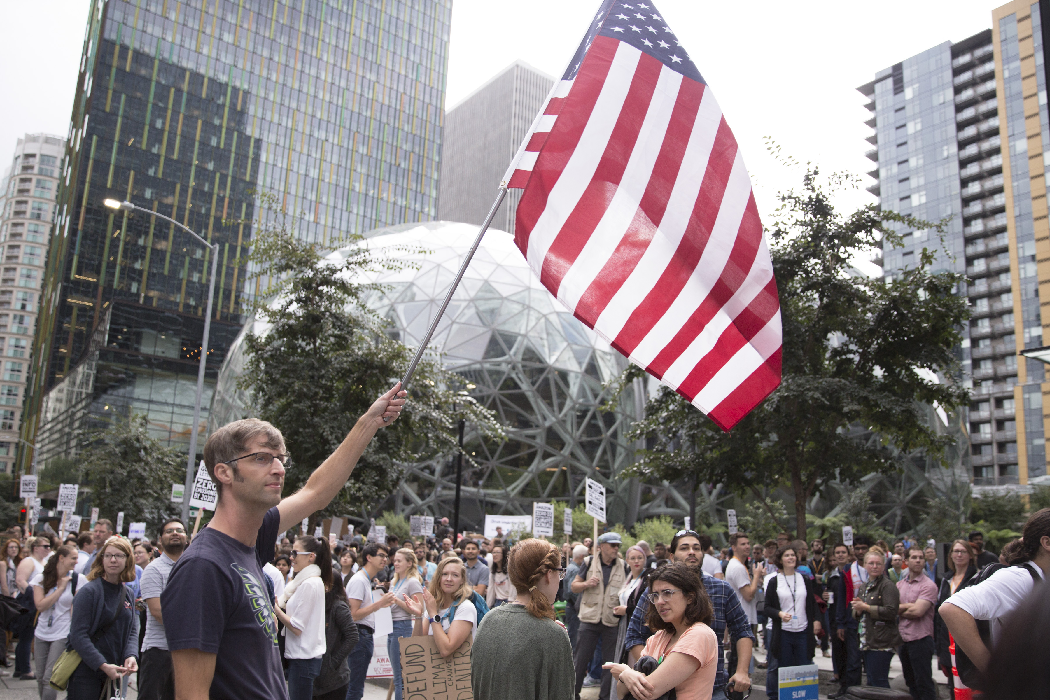 An Amazon employee holds an American flag outside the company's Seattle headquarters.