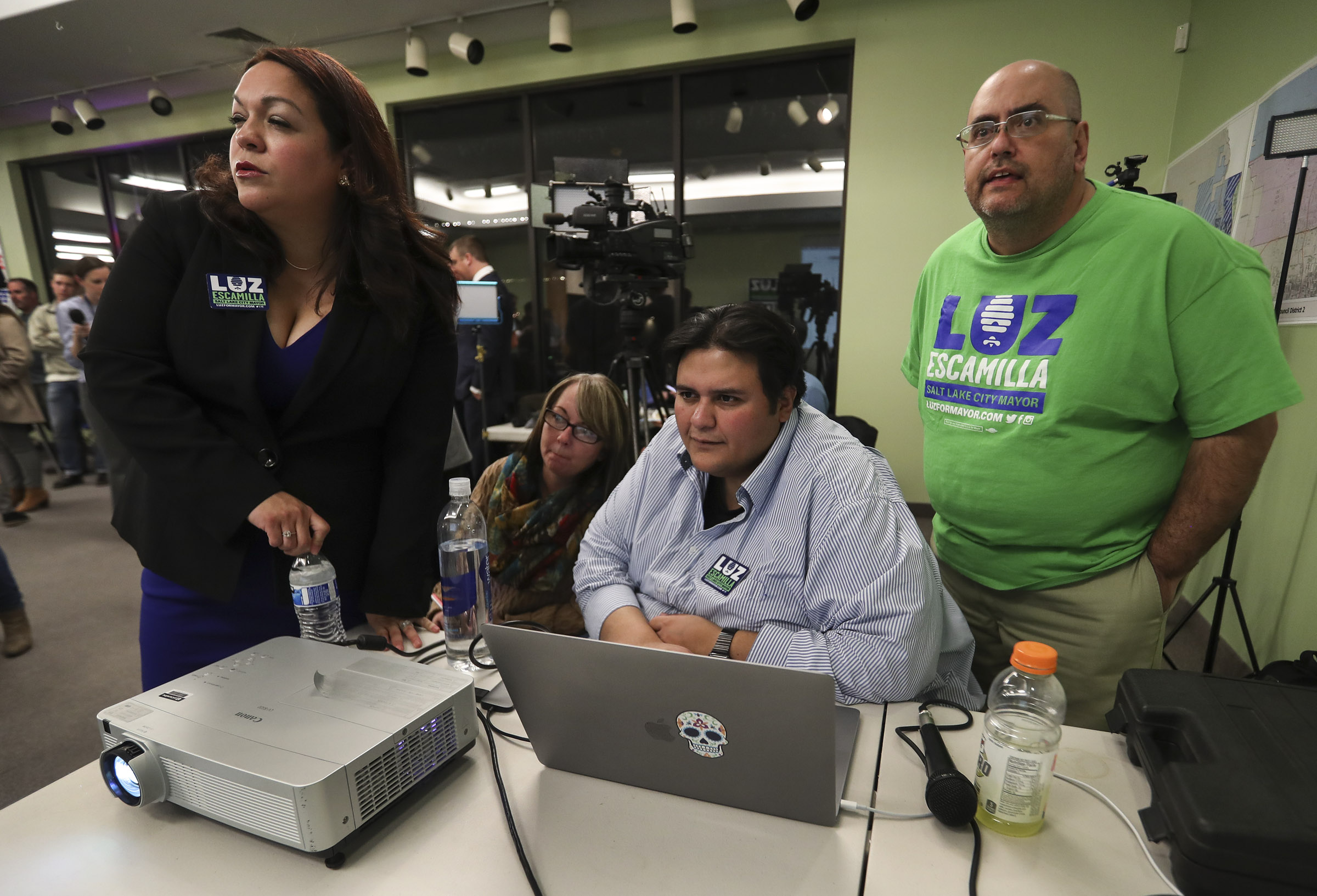 Salt Lake City mayoral candidate and state Sen. Luz Escamilla, left, looks at results that are projected on a screen with volunteer Tracy Taylor, campaign field director Richard Jaramillo, and volunteer Ernie Gamonal from her election night headquarters in Salt Lake City on Tuesday, Nov. 5, 2019.