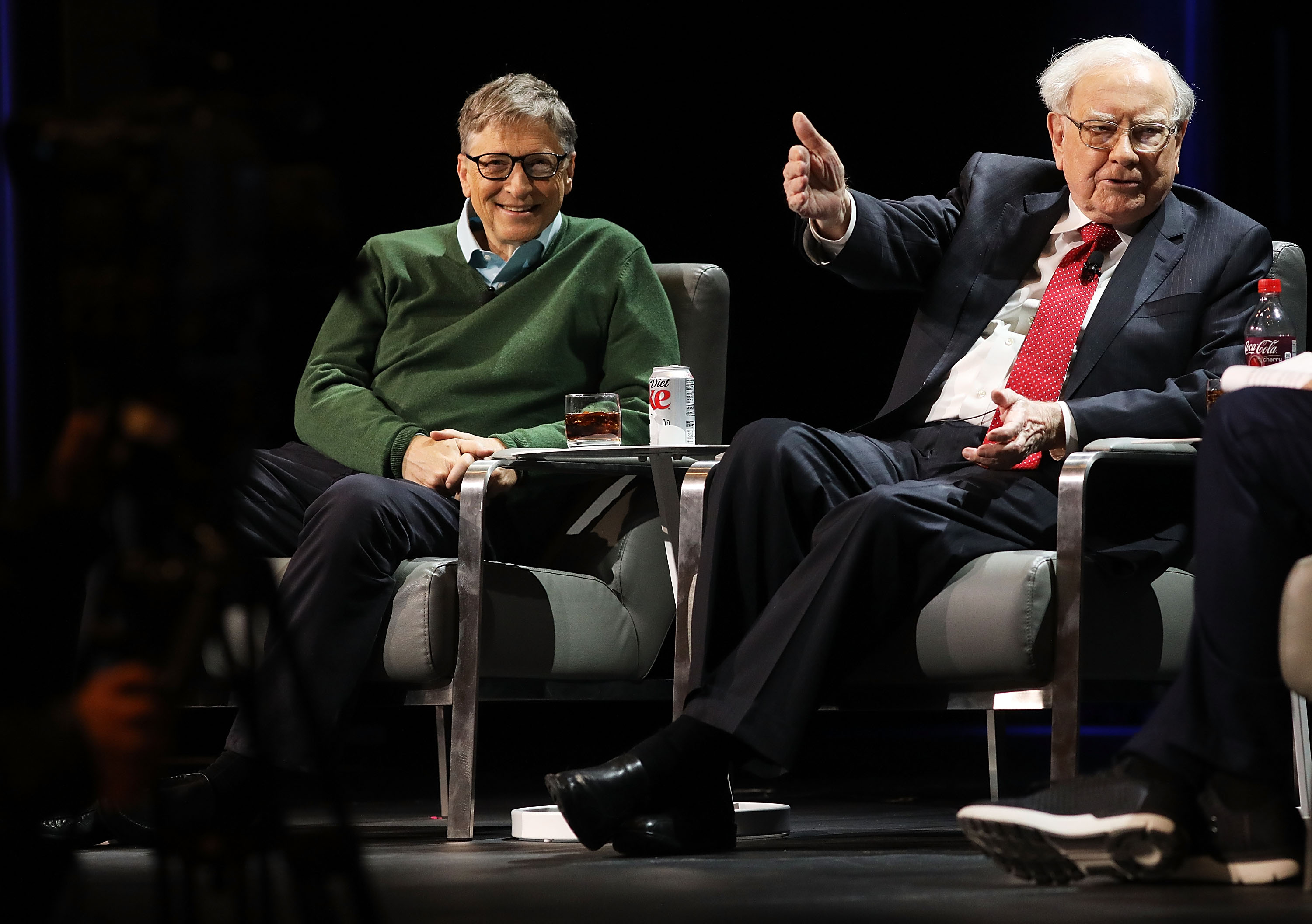 Bill Gates seated next to Warren Buffett onstage at a conference.
