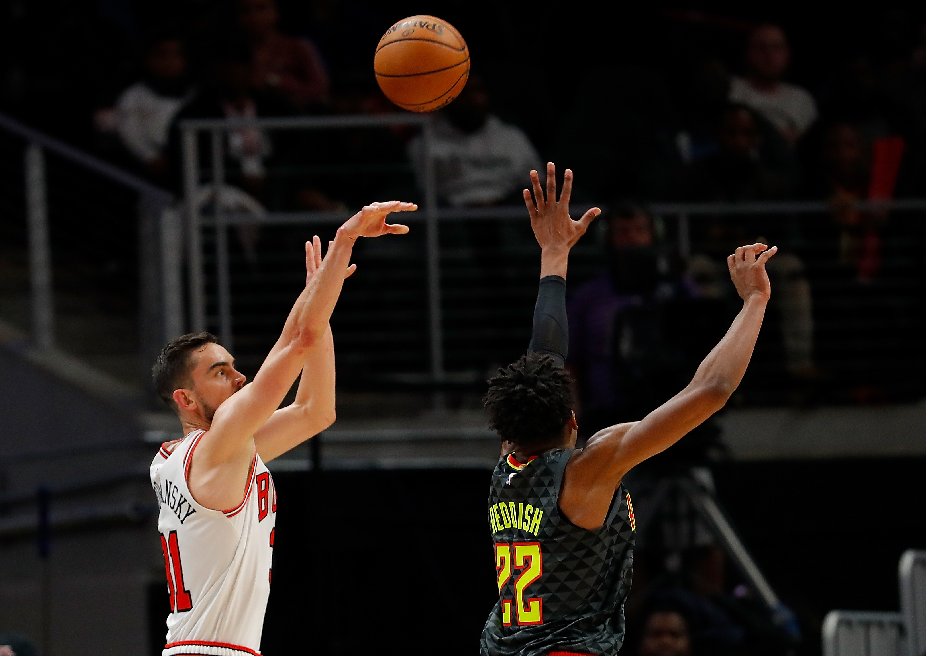 The Bulls' Tomas Satoransky shoots a three-point basket over Cam Reddish of the Hawks as time expires at the end of the first half on Wednesday.